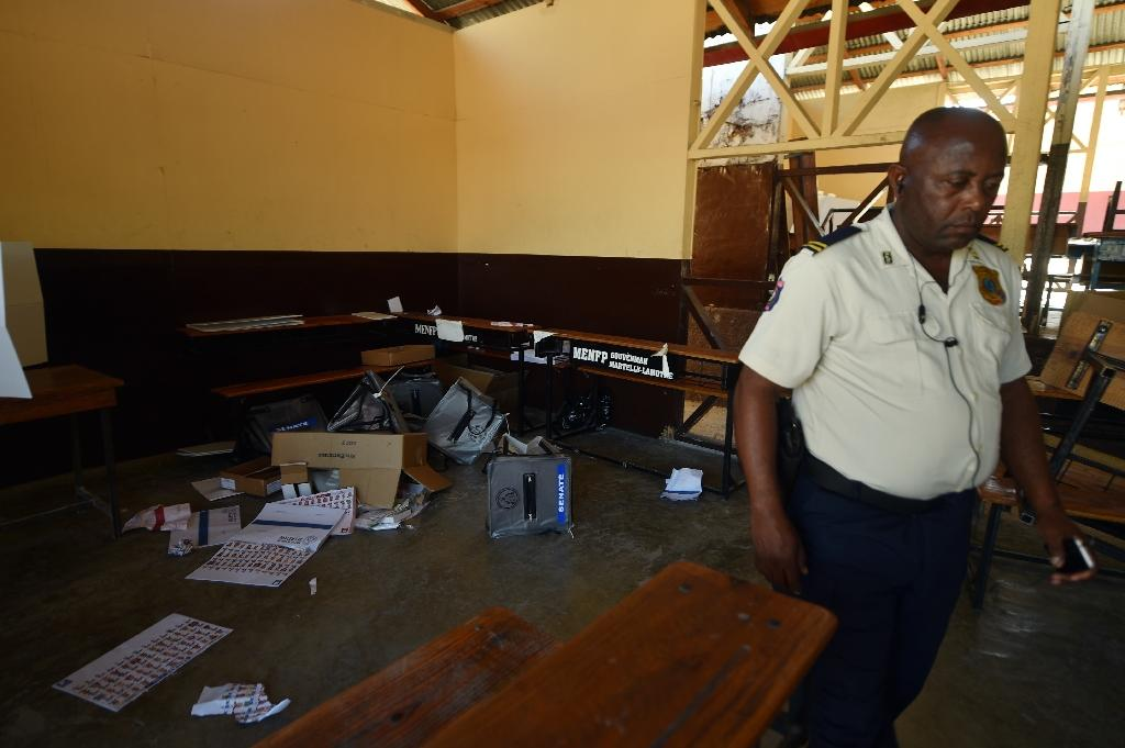 A torn ballots and ballot box are seen on the floor of a voting station after a group of people entered and and began tearing them up during the Legislative Elections in Port-au-Prince on August 9, 2015 (AFP Photo/Hector Retamal)