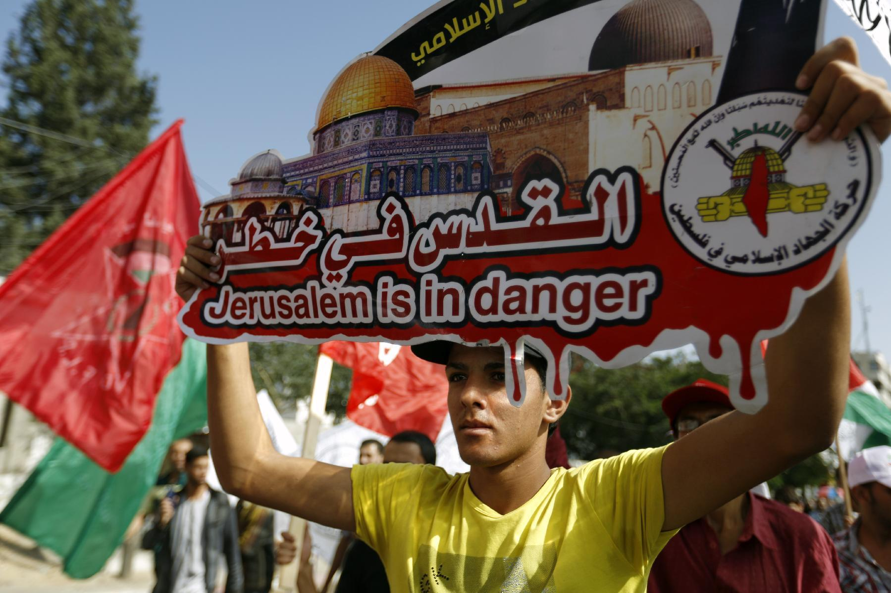 """A Palestinian holds a placard reading """"Jerusalem is in danger"""" during a rally to protest after authorities restricted access to the al-Aqsa mosque compound on October 17, 2014 in Gaza City (AFP Photo/Mohammed Abed)"""