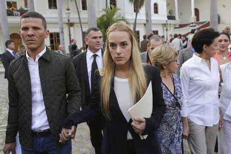 FILE PHOTO: Lilian Tintori (C), wife of jailed opposition leader Leopoldo Lopez, holds hands with opposition deputy Gilbert Caro (L) as she leaves after a meeting with deputies of the Venezuelan coalition of opposition parties (MUD) and relatives of imprisoned dissidents at the National Assembly in Caracas, January 11, 2016. REUTERS/Marco Bello/File Photo