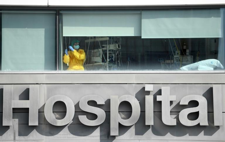 """A healthcare worker looks out the window of La Paz hospital, in Madrid, as Spain's health minister calls on residents of the city to limit their movements and social contacts to the """"essential"""""""