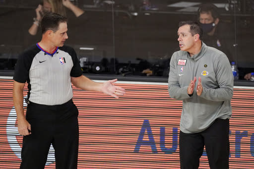 Los Angeles Lakers head coach Frank Vogel, right, talks with an official during the first half of an NBA conference final playoff basketball game against the Denver Nuggets Thursday, Sept. 24, 2020, in Lake Buena Vista, Fla. (AP Photo/Mark J. Terrill)