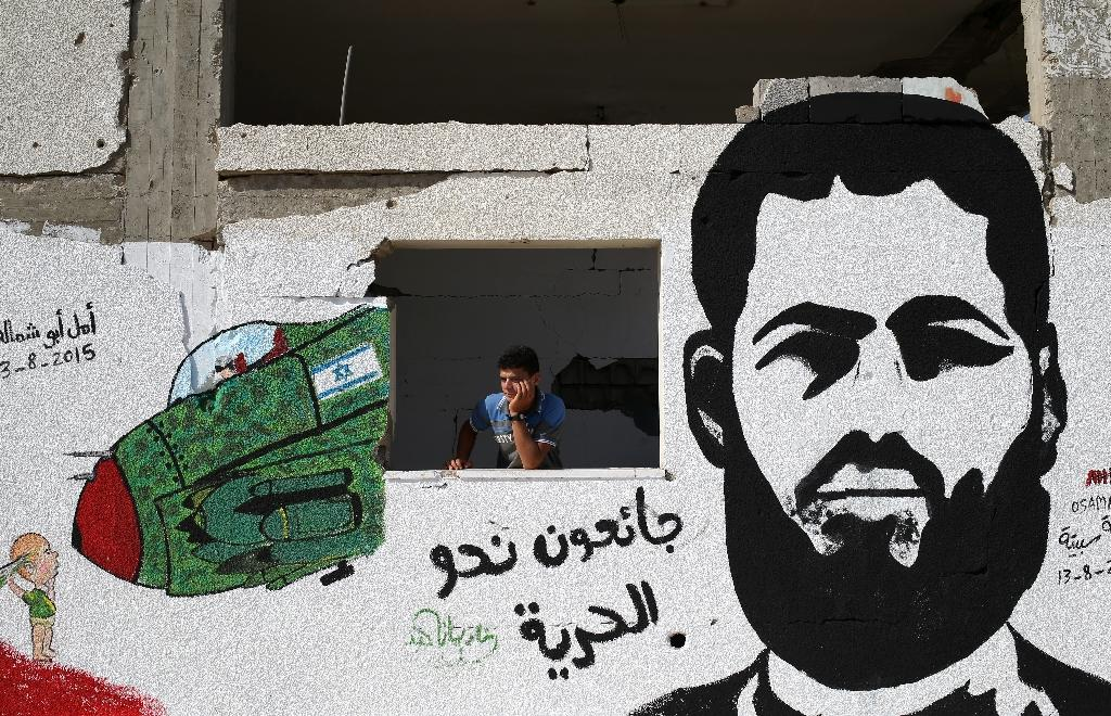 A youth stands behind a wall sprayed with graffiti depicting Mohammed Allan, a Palestinian held by Israel without trial, on August 16, 2015 in Gaza City (AFP Photo/Mohammed Abed)