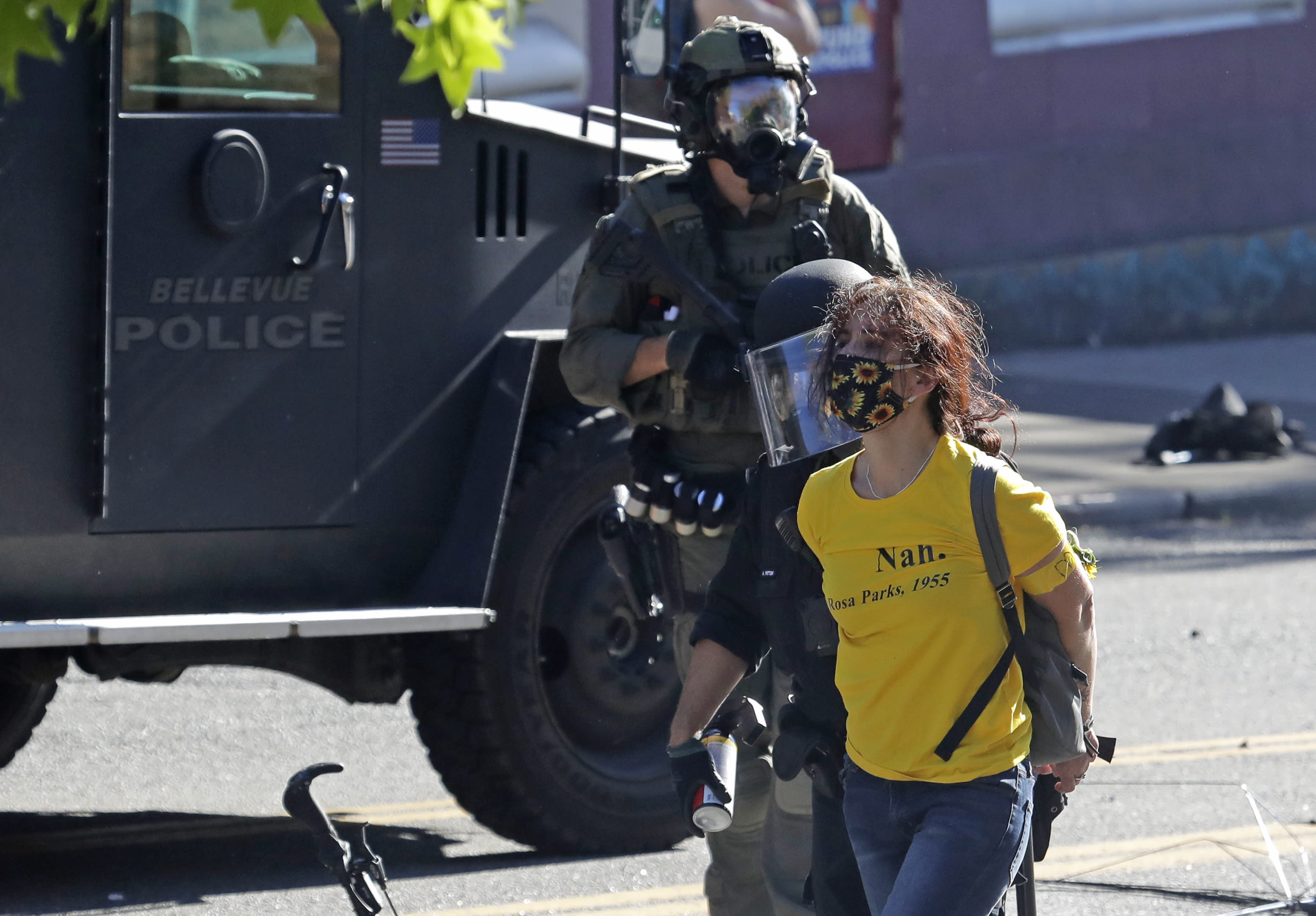 """Police arrest a person wearing a yellow shirt an armband that reads """"Mom,"""" Saturday, July 25, 2020, during a Black Lives Matter protest near Seattle Central Community College in Seattle. A large group of protesters were marching Saturday in Seattle in support of Black Lives Matter and against police brutality and racial injustice. (AP Photo/Ted S. Warren)"""