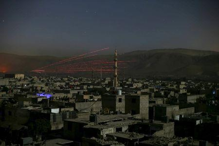 Fire trails seen during clashes between forces loyal to Syria's President Bashar al-Assad and the Army of Islam fighters, on the eastern mountains of Qalamoun overlooking the town of Douma, eastern Ghouta in Damascus