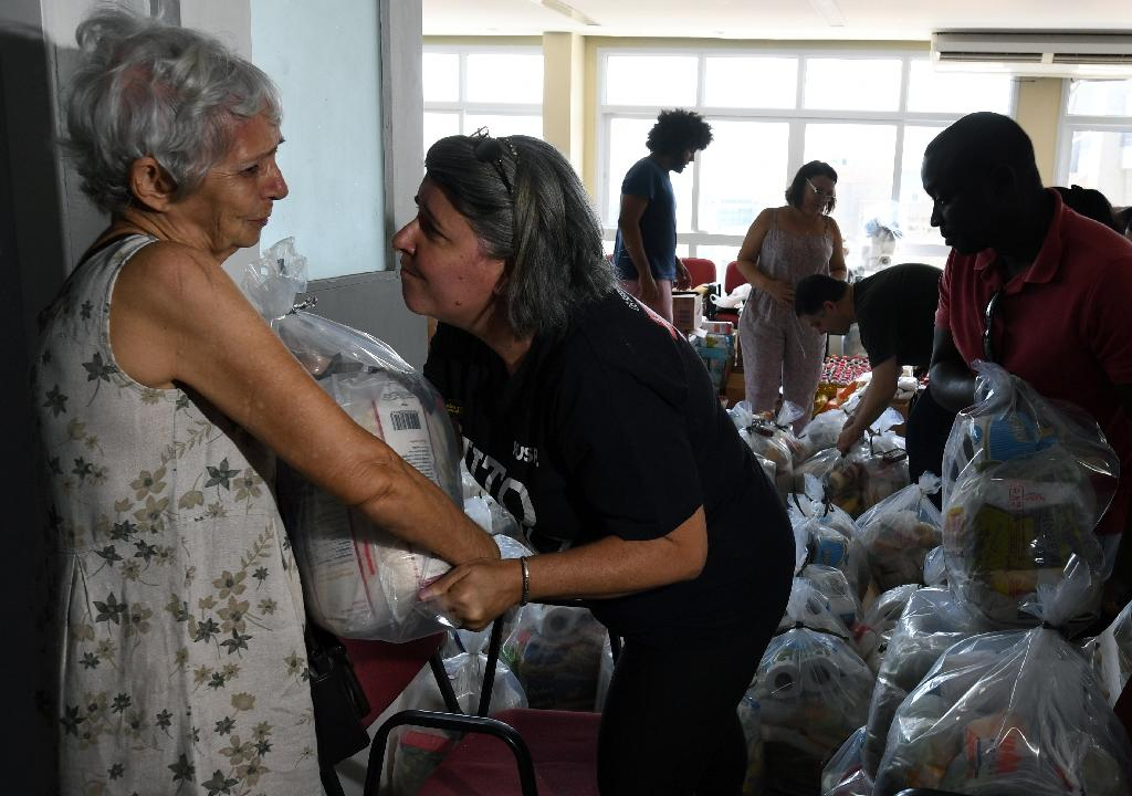 A volunteer from a government workers' union comforts an elderly civil servant while giving her a food donation in Rio (AFP Photo/VANDERLEI ALMEIDA)