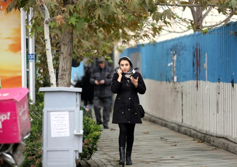 A woman makes a cell phone call while walking along a street in Tehran (AFP Photo/ATTA KENARE)