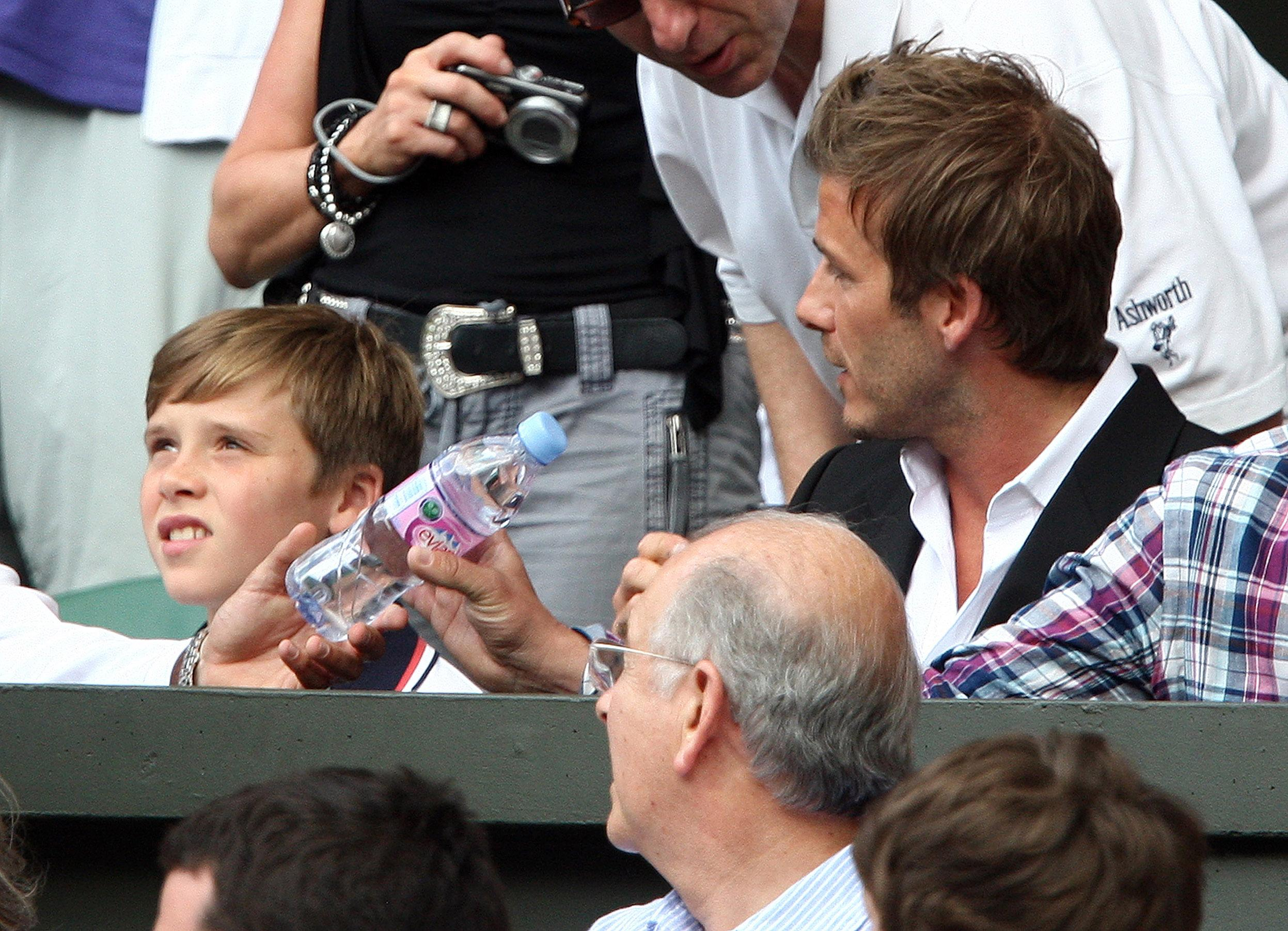 Tennis - Wimbledon - All England Lawn Tennis & Croquet Club, Wimbledon, England - 2/7/10  David Beckham (R) with his son Brooklyn in the stands during Great Britain's Andy Murray  semi final match  Mandatory Credit: Action Images / Paul Childs  Livepic