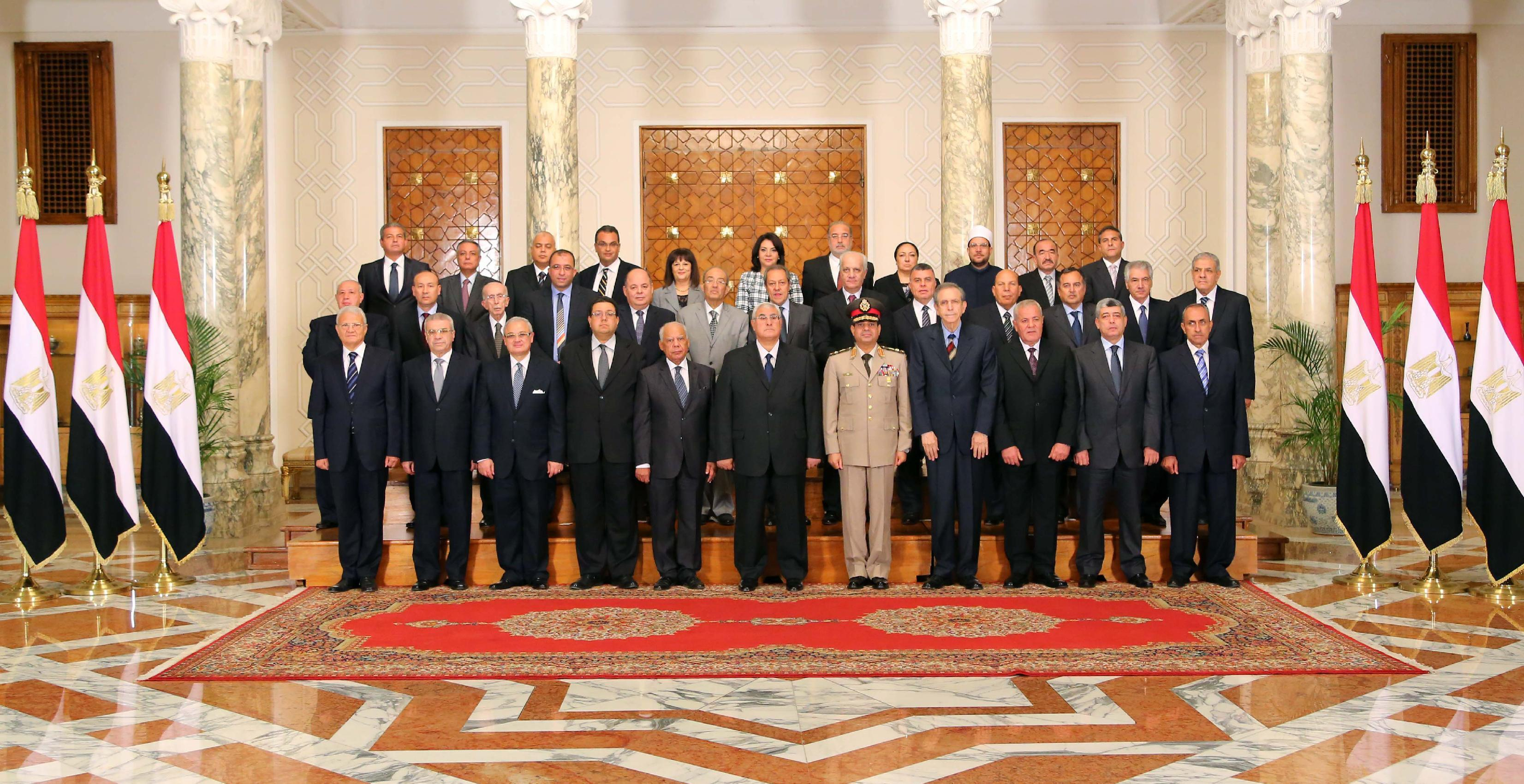 This image released by the Egyptian Presidency on Tuesday, July 16, 2013 shows interim President Adly Mansour, center, with his new cabinet ministers at the presidential palace in Cairo, Egypt. Egypt's interim president has sworn in a new Cabinet, the first since the ouster of the Islamist president by the military nearly two weeks ago. The new government, sworn in Tuesday, is led by Prime Minister Hazem el-Beblawi, an economist, and features the promotion of Defence Minister Gen. Abdel-Fattah el-Sissi, who ousted Mohammed Morsi on July 3, to deputy prime minister. He also retains the defence portfolio. (AP Photo/Egyptian Presidency)