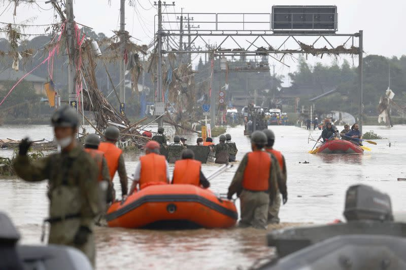 Local residents are rescued by Japanese Self-Defence Force soldiers using a boat at a flooding area caused by a heavy rain in Kuma village