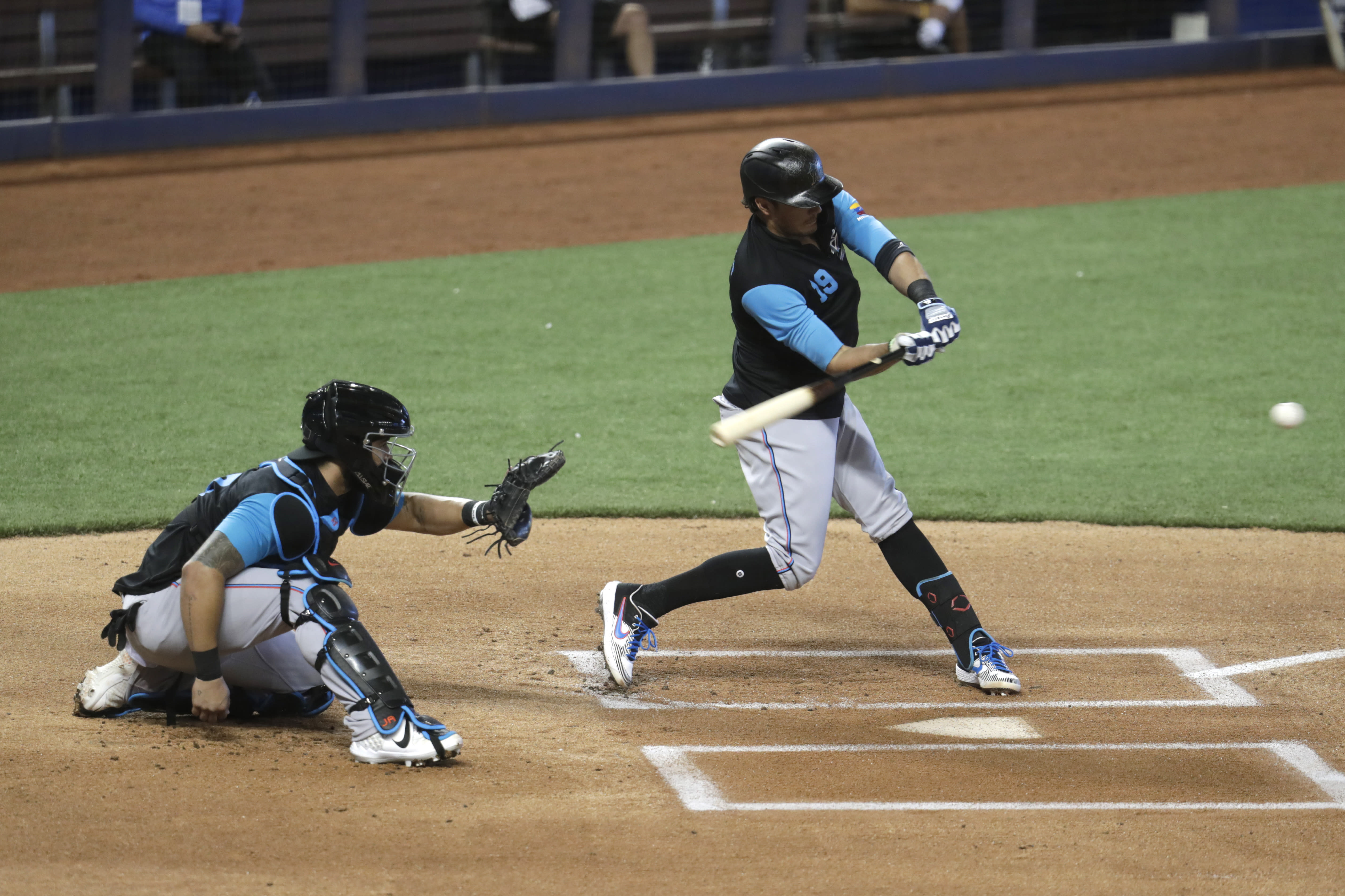 Miami Marlins shortstop Miguel Rojas (19) bats as Jorge Alfaro catches during baseball practice at Marlins Park, Wednesday, July 8, 2020, in Miami. (AP Photo/Lynne Sladky)