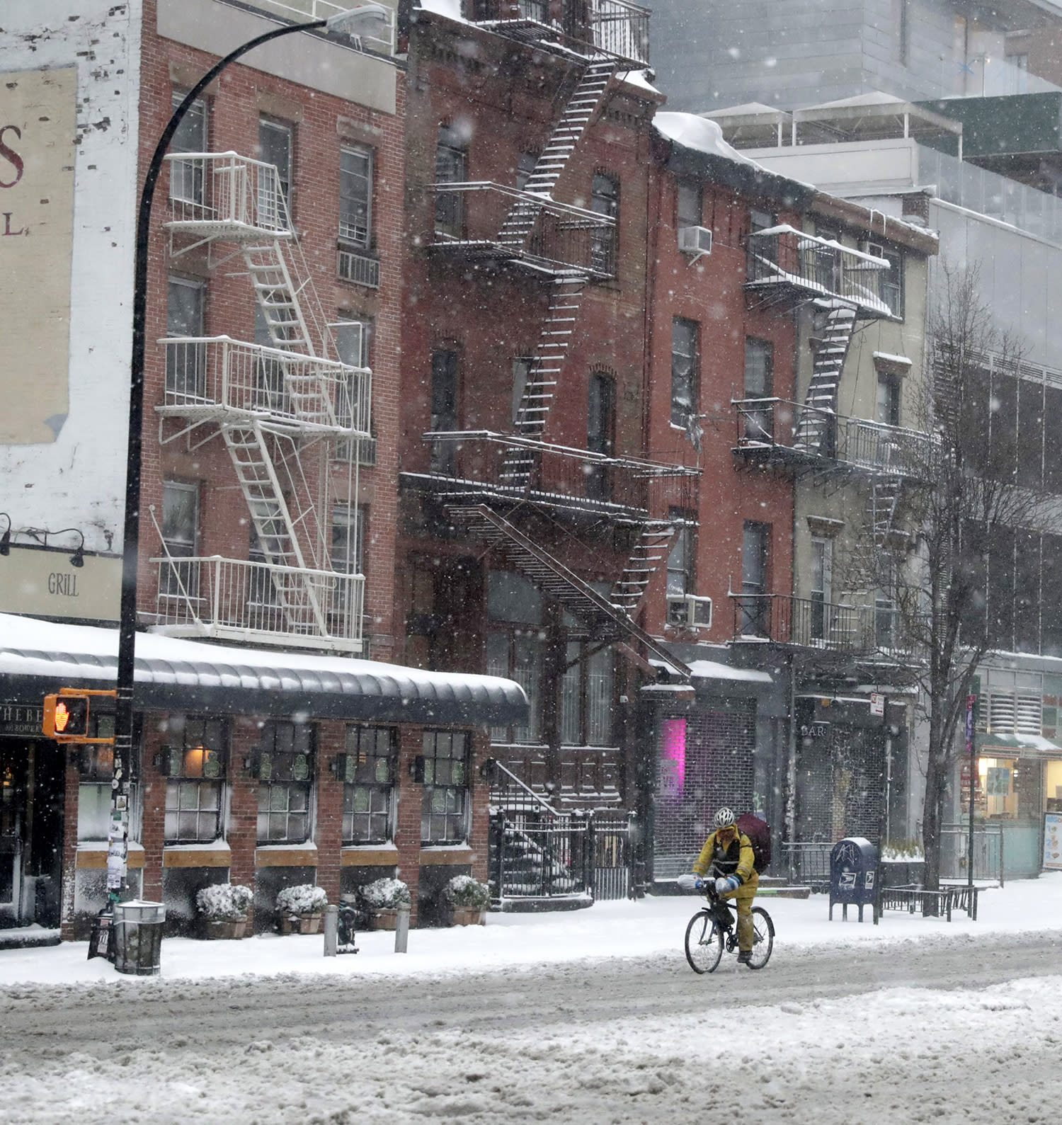 <p>A delivery man rides on his bike through the snow on the Bowery in New York, March 14, 2017. While New York and Boston had been issued a blizzard warning, that has been downgraded to a winter storm as the storm's track shifted resulting in a shift to rain for both cities and smaller forecast snowfall totals. (Jason Szenes/EPA) </p>