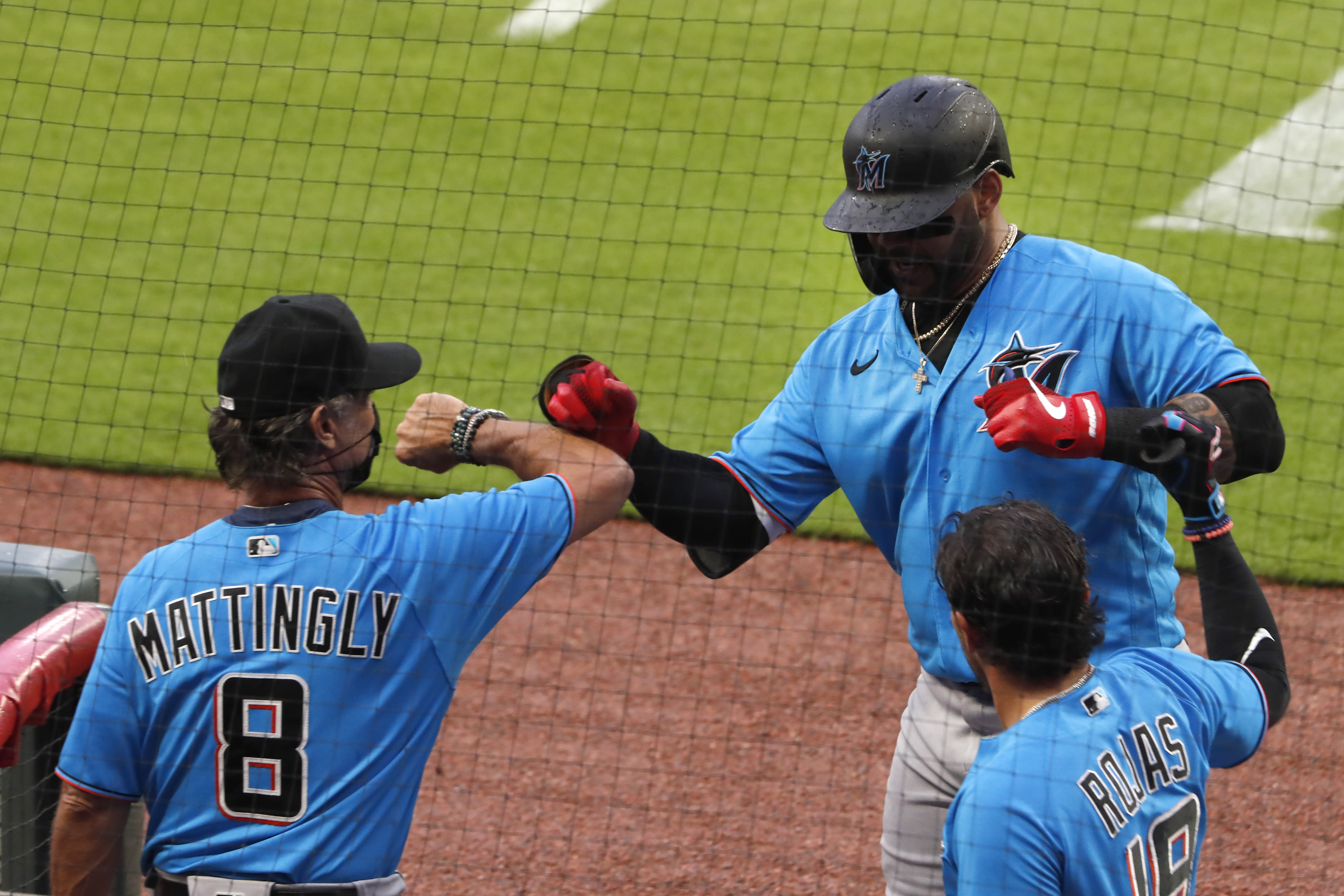 Miami Marlins' Jonathan Villar (2), center, is greeted a the dugout by Miami Marlins manager Don Mattingly (8) after hitting a home run in the third inning of an exhibition baseball game against the Atlanta Braves Tuesday, July 21, 2020, in Atlanta. (AP Photo/John Bazemore)