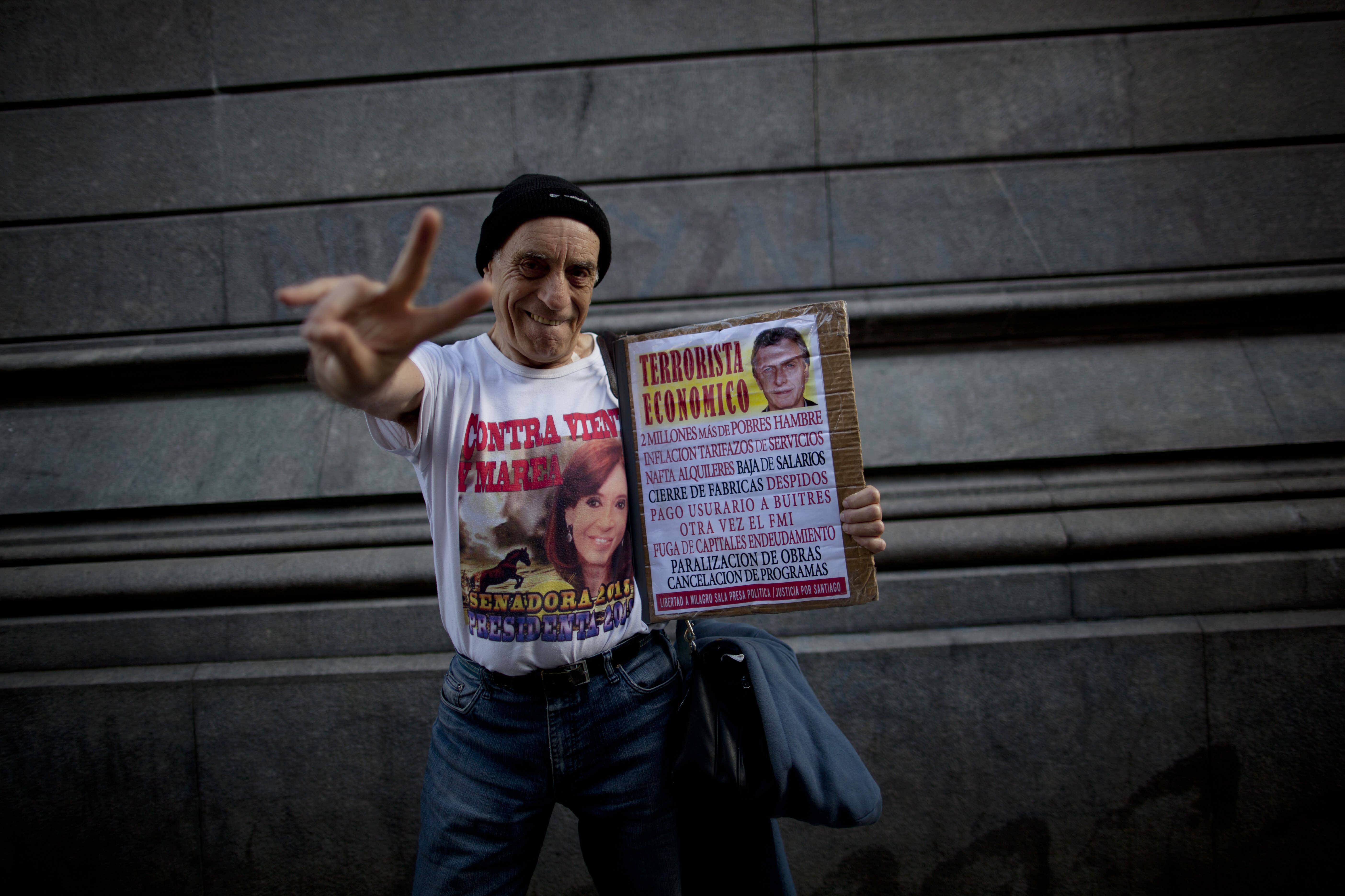"""In this Oct. 3, 2018 photo, philosophy professor Juan Carlos Amarfil, 67, strikes a pose wearing a T-shirt emblazoned with an image of former President Cristina Fernandez, as he holds a poster headlined, """"Economic terrorist"""" next to an image of President Maurcio Macri, during a demonstration demanding improved conditions for disabled retirees, in Buenos Aires, Argentina. Cries of support for Fernandez, who is now serving as a senator, continue to rise from crowds during protests against the austerity policies of Macri, the conservative who replaced her as leader of Argentina. (AP Photo/Natacha Pisarenko)"""