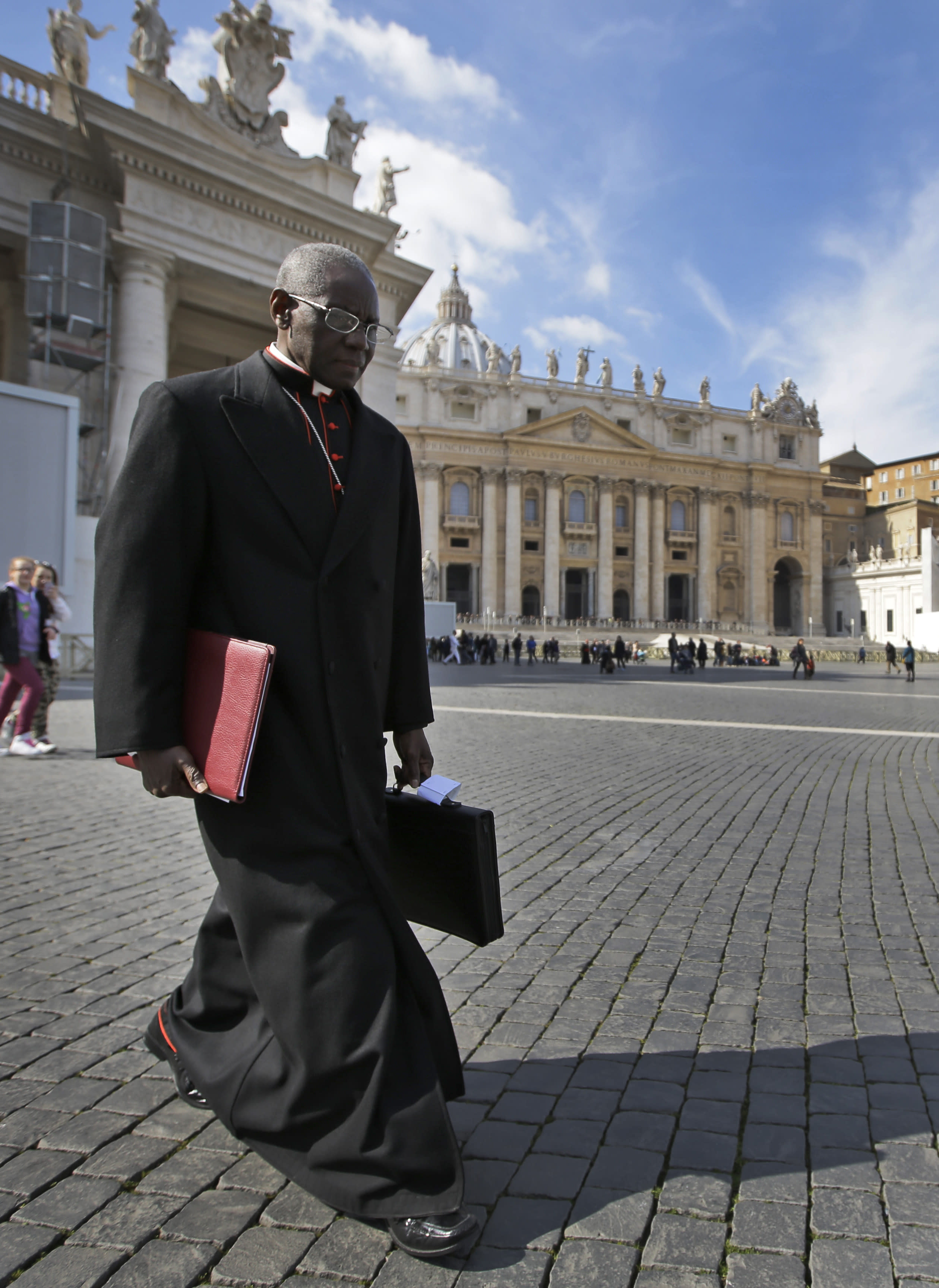 """FILE - In this Monday, March 4, 2013 file photo, Cardinal Robert Sarah, of Guinea, walks in St. Peter's Square after attending a cardinals' meeting, at the Vatican. Retired Pope Benedict XVI wrote the book, """"From the Depths of Our Hearts: Priesthood, Celibacy and the Crisis of the Catholic Church,"""" along with his fellow conservative, Guinean Cardinal Robert Sarah, who heads the Vatican's liturgy office and has been a quiet critic of Francis. (AP Photo/Andrew Medichini, File)"""