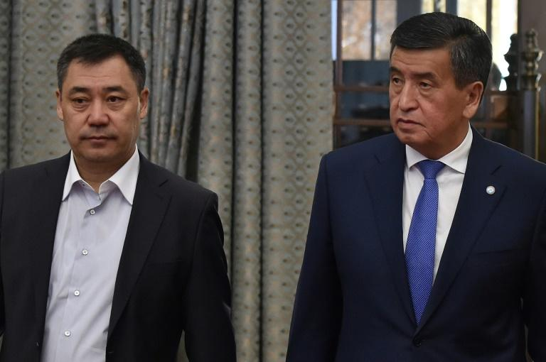 Kyrgyzstan's recently-appointed Prime Minister Sadyr Japarov (L) and former President Sooronbay Jeenbekov (R) walk into the Kyrgyz Parliament extraordinary meeting at Ala-Archa state residence in Bishkek on Friday