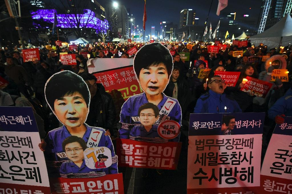 Protesters carry portraits of impeached South Korean President Park Geun-Hye during a protest in Seoul