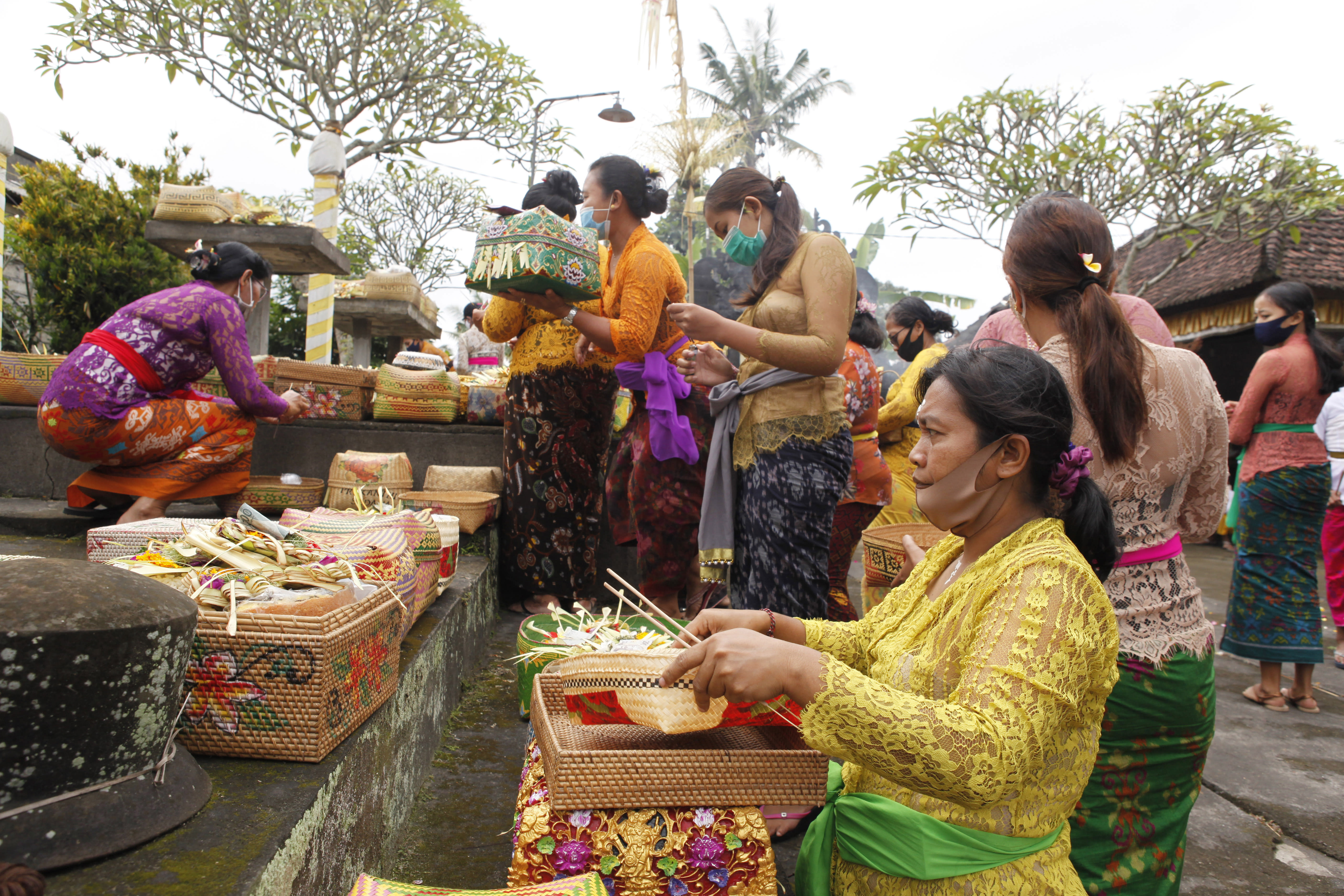 Women wearing face masks as a precaution against the new coronavirus outbreak participate in a Hindu ritual at a temple in Bali, Indonesia, Wednesday, Sept. 16, 2020. (AP Photo/Firdia Lisnawati)