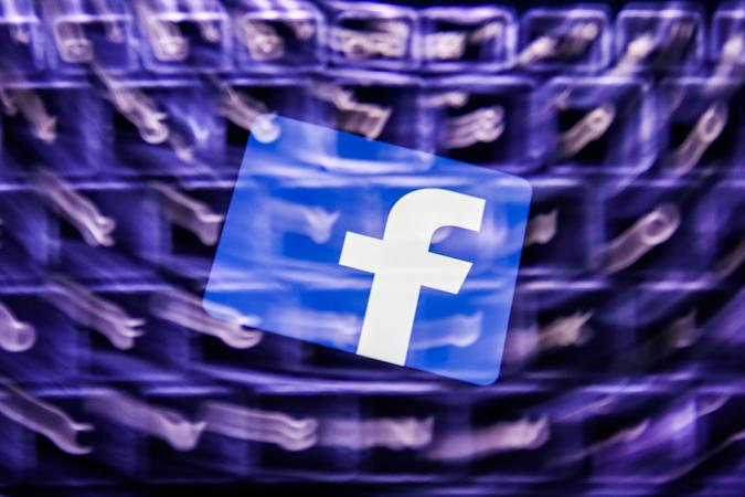 Facebook logo displayed on a phone screen and a keyboard are seen in this multiple exposure illustration photo taken in Poland on February 8, 2021. Facebook reacted negatively to Apple's privacy policy changes. (Photo illustration by Jakub Porzycki/NurPhoto via Getty Images)