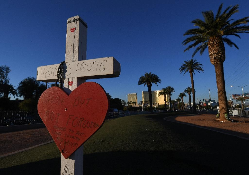 A solitary cross remained on November 15, 2017 at a Las Vegas memorial site in front of the Mandalay Bay hotel (background) for the 58 victims of the worst mass shooting in recent US history