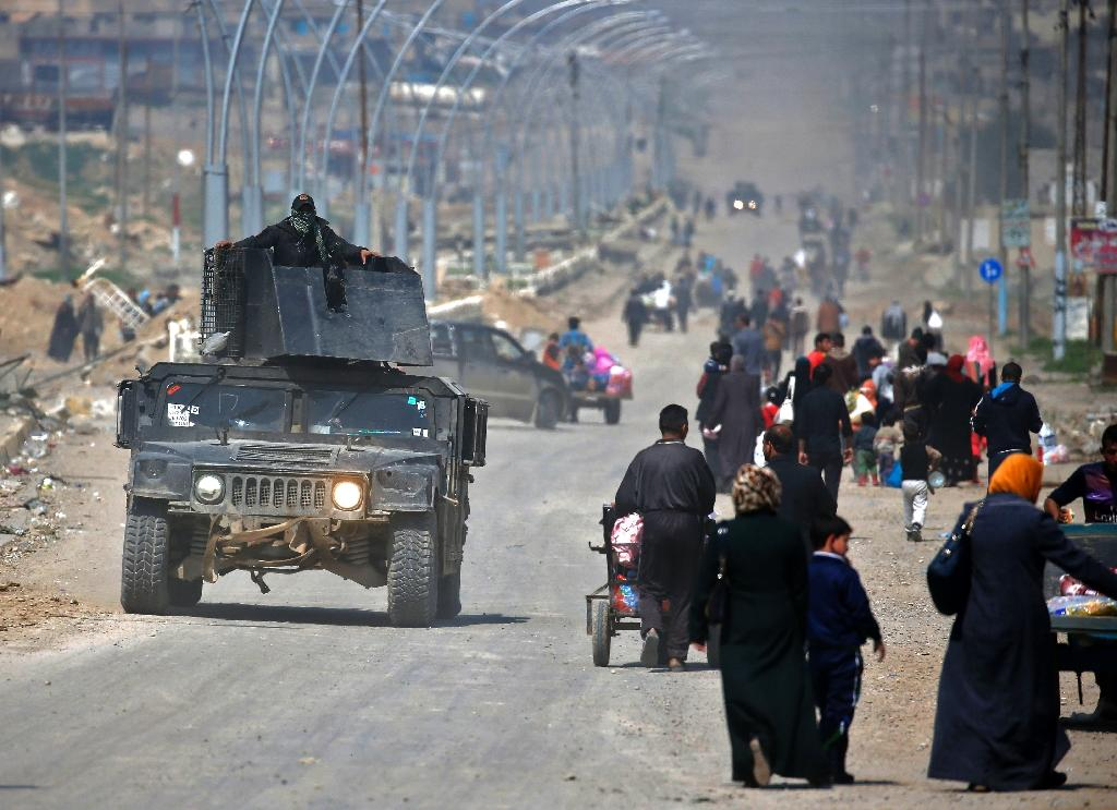 Iraqi security forces drive past civilians fleeing their homes in Mosul's old city on March 30, 2017, due to the ongoing battles between government forces and Islamic State group fighters (AFP Photo/AHMAD GHARABLI)