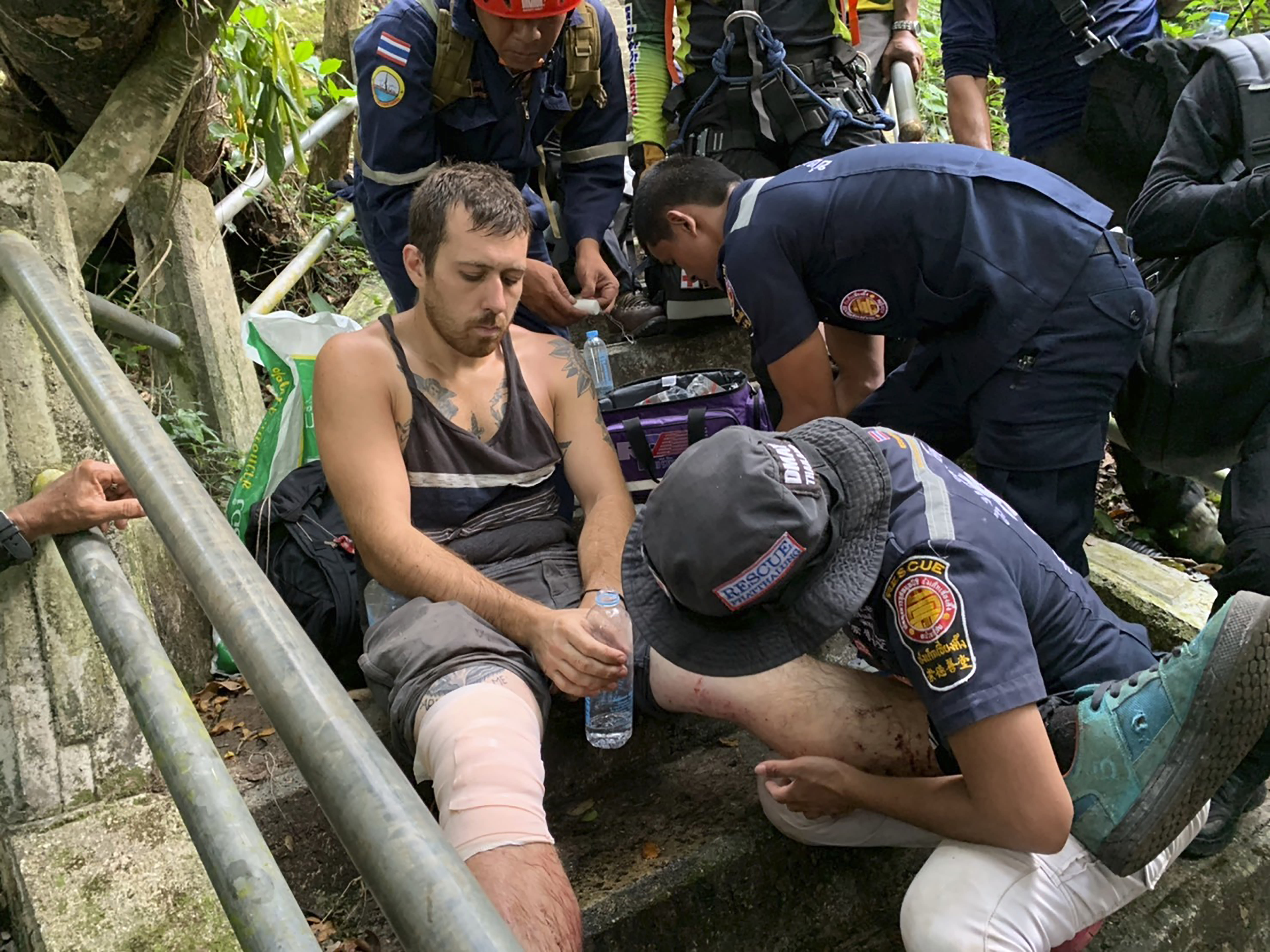 In this image released by the Phattalung Rescue Organization, a base jumper is treated after being rescued from the edge of a cliff, Monday, Jan. 13, 2020, in Phattalung, Thailand. An Austrian base jumper, Johannes Grasser, 28, was rescued in the southern Thai province after being stuck on a near vertical cliff for hours when his parachute caught a rock's edge, almost 200 meters (656 feet) above the around. (Phattalung Rescue Organization via AP)