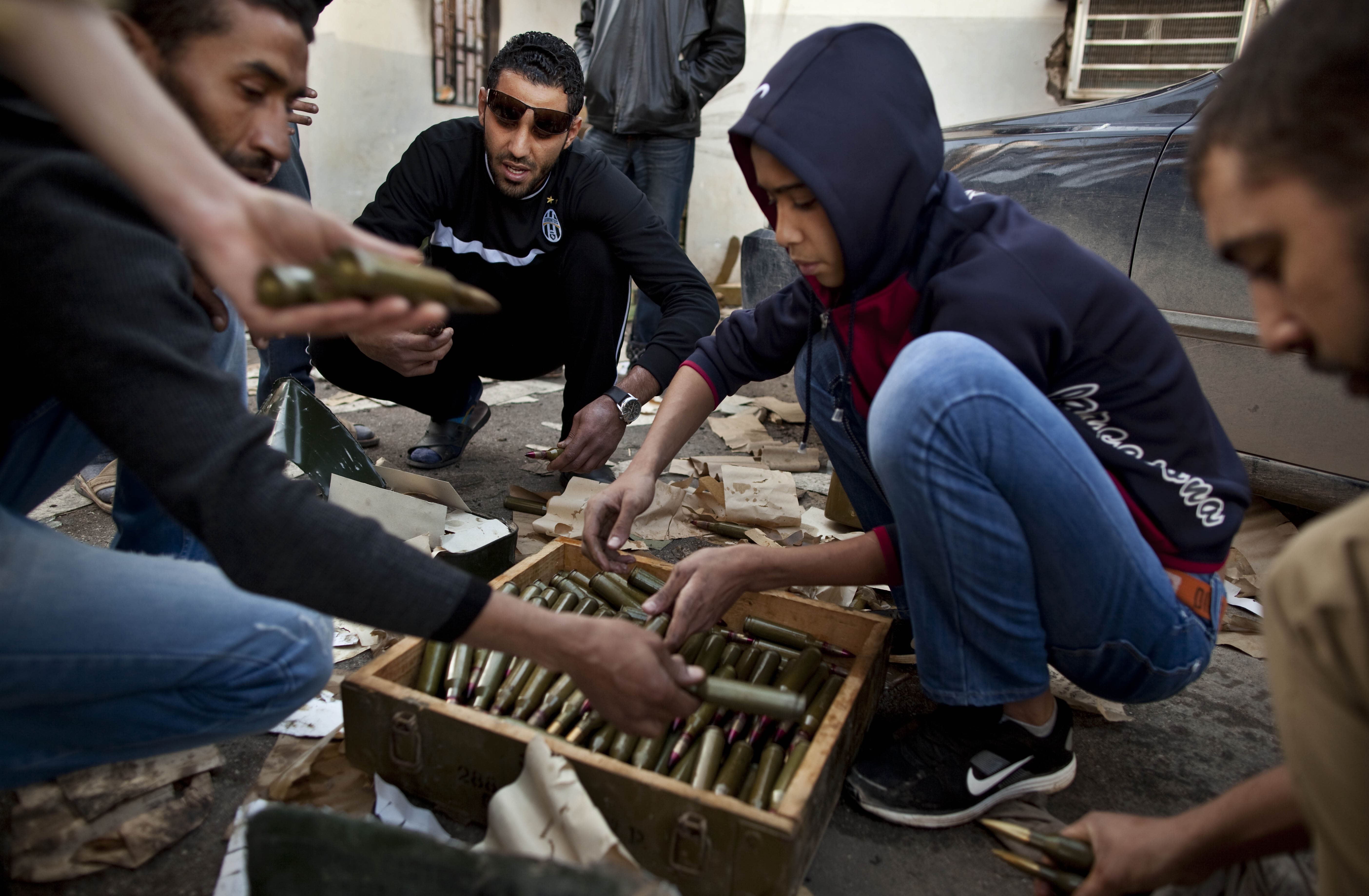 FILE - In this Monday, Feb. 28, 2011 file photo, Libyan militia members who are part of the forces against Libyan leader Moammar Gadhafi organize their munitions at a military base in Benghazi, eastern Libya. At the heart of the Libyan capital, the open-air Fish Market was once where residents went to buy everything from meat and seafood to clothes and pets. Now it's Tripoli's biggest arms market, with tables displaying pistols and assault rifles. Ask a vendor, and he can pull out bigger machine guns to sell for thousands of dollars. (AP Photo/Kevin Frayer, File)