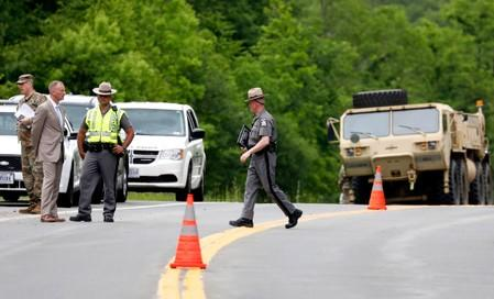 Military personnel and state police talk at the scene of a road block after a military training accident in an area near the U.S. Military Academy in West Point