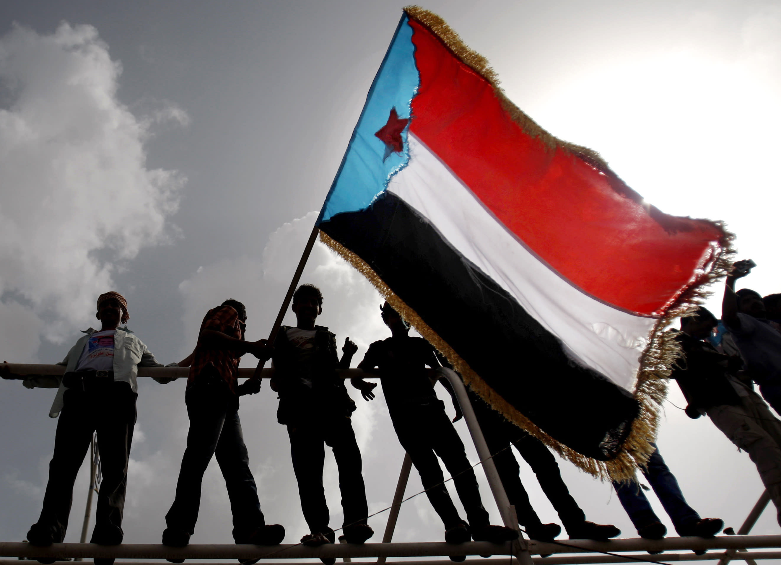 FILE - In this Jan. 13, 2013 file photo, Yemeni supporters of the Southern Separatist Movement hold a flag of the former South Yemen, during a rally in Aden, Yemen. Fighting between their allies in southern Yemen has opened a gaping wound in the Saudi Arabia and the United Arab Emirates' coalition fighting the country's rebels. If they can't fix it, it threatens to further fragment the country into smaller warring pieces. (AP Photo/Hani Mohammed, File)