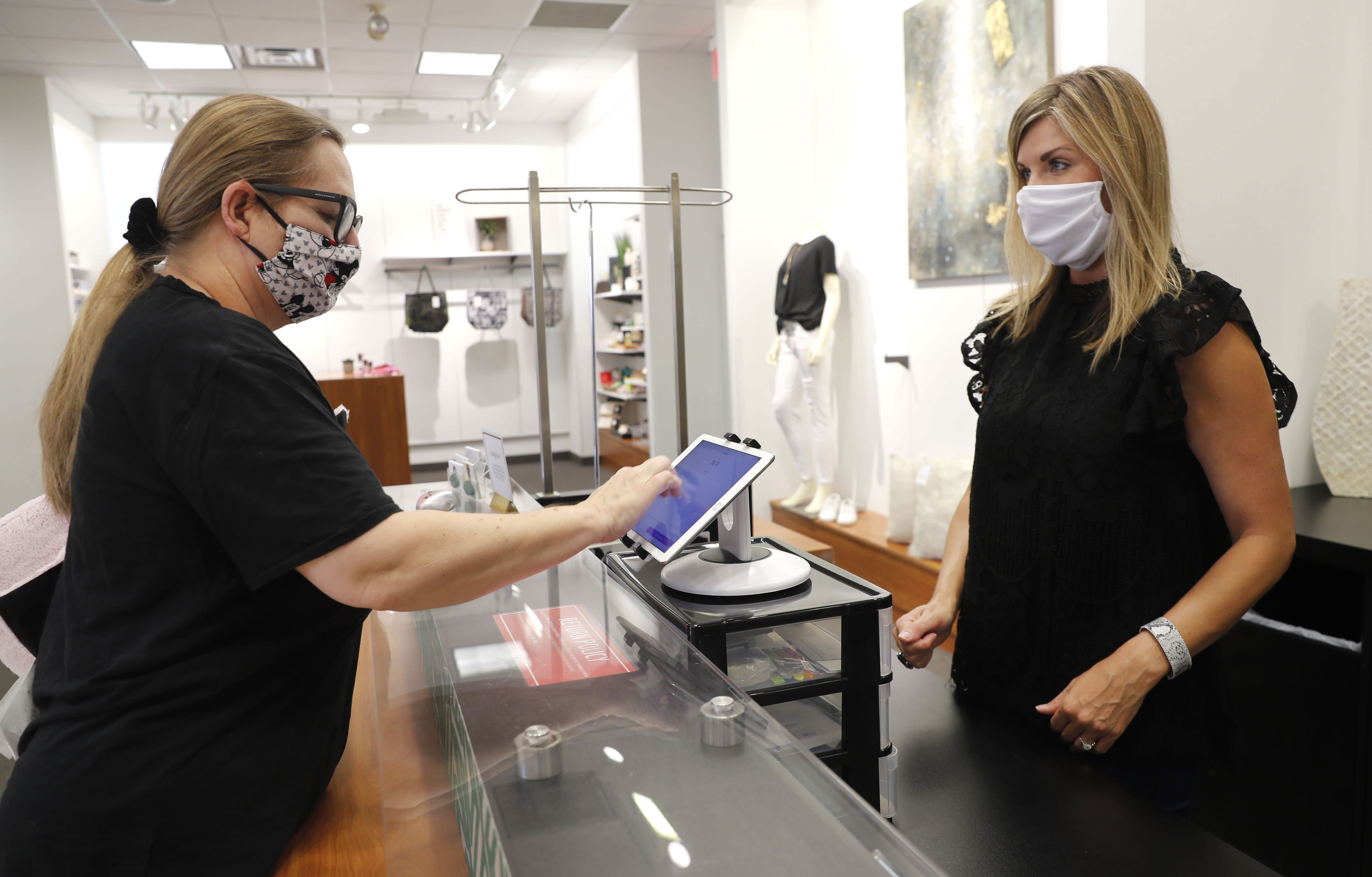 """FILE In this Wednesday, May 13, 2020 FILE photo, Monique Kursar, left, completes a purchase with Amy Witt, owner of the Velvet Window, in Dallas. For small retailers across the country, the coronavirus outbreak has turned an already challenging business environment into never-ending uncertainty. Witt might have 20 customers on a good day in her women's clothing store, and then none the next. """"It's a rollercoaster we ride every day,"""" says Witt (AP Photo/LM Otero)"""