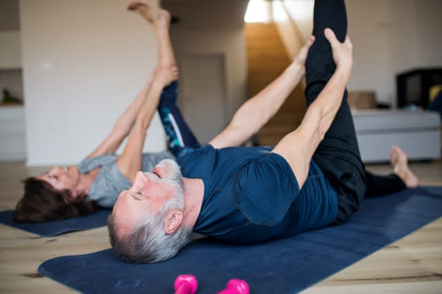 A senior couple indoors at home, doing exercise in living room.