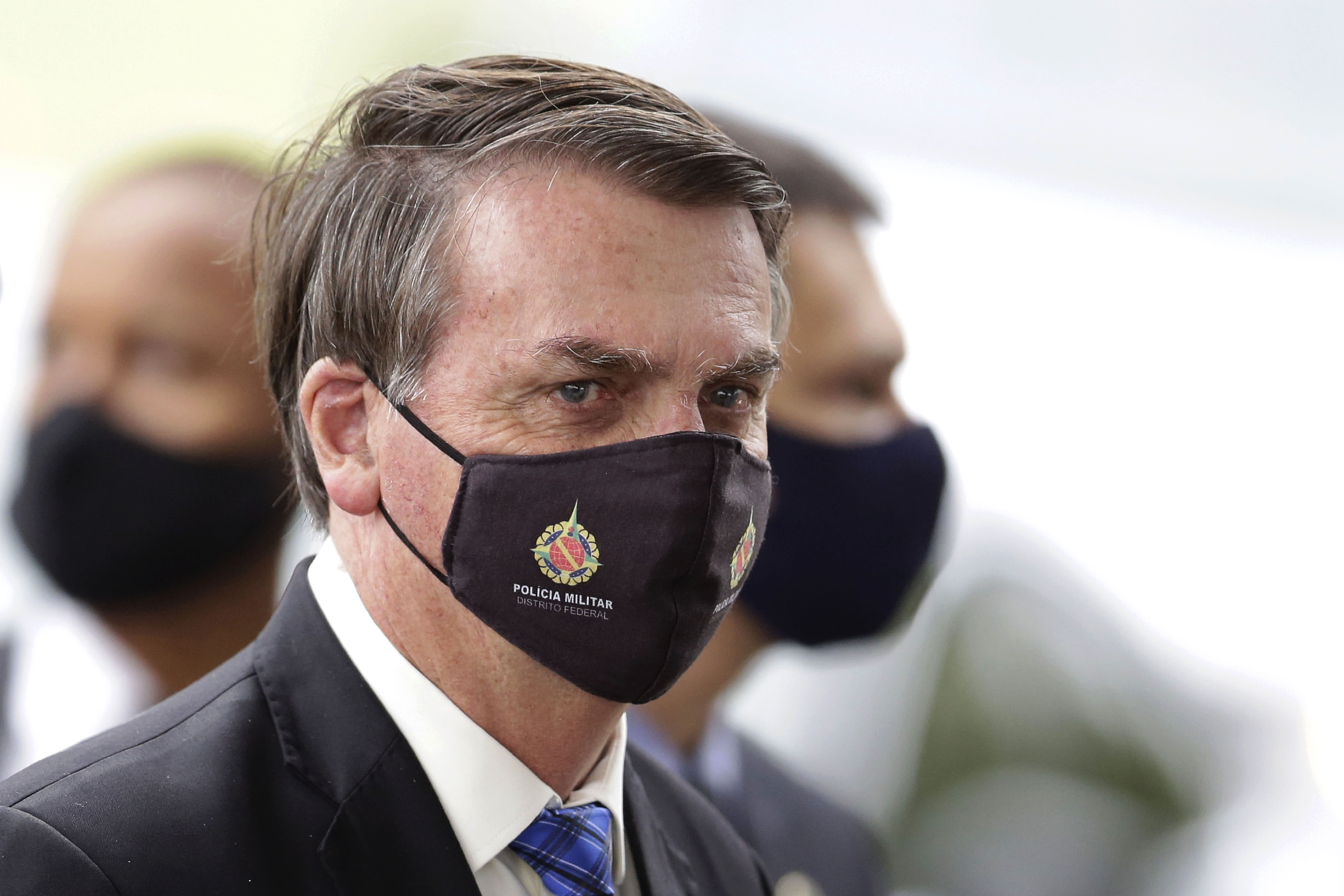 """FILE - In this May 18, 2020, file photo, Brazilian President Jair Bolsonaro wears a mask due to the coronavirus pandemic as he talks with supporters upon departure from his official residence, Alvorada palace, in Brasilia, Brazil. The logo on the mask reads """"Military Police. Federal District."""" After 35 years of civilian-led democracy, Bolsonaro has created the most militarized Brazilian government since the fall of the country's army-led dictatorship. (AP Photo/Eraldo Peres, File)"""
