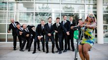 Woman on scooter rides through groomsmen group photo in epic photobomb