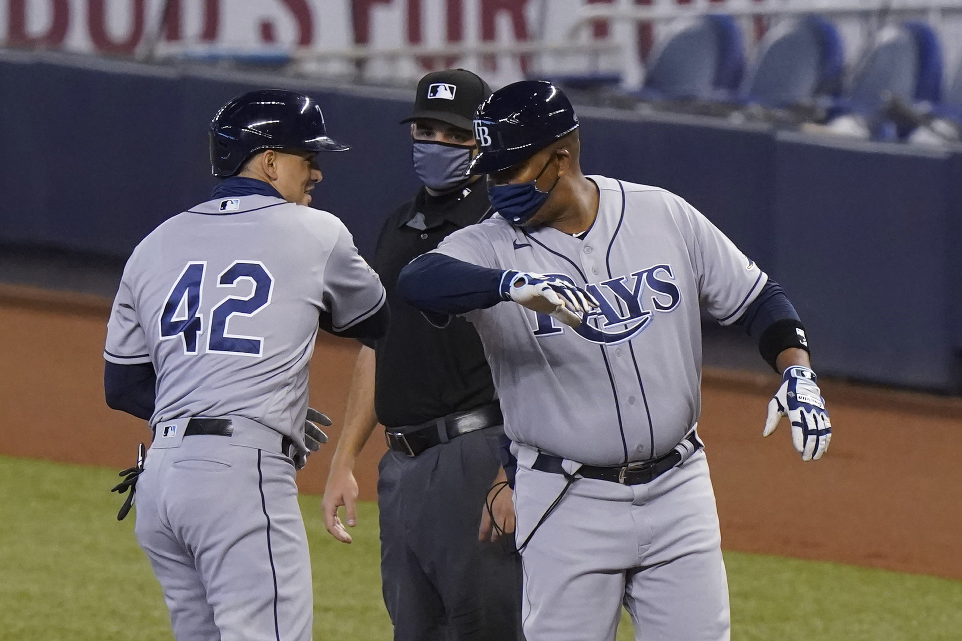Tampa Bay Rays' Willy Adames, left, is congratulated by first base coach Ozzie Timmons after getting a base hit during the first inning of a baseball game against the Miami Marlins, Sunday, Aug. 30, 2020, in Miami. (AP Photo/Wilfredo Lee)
