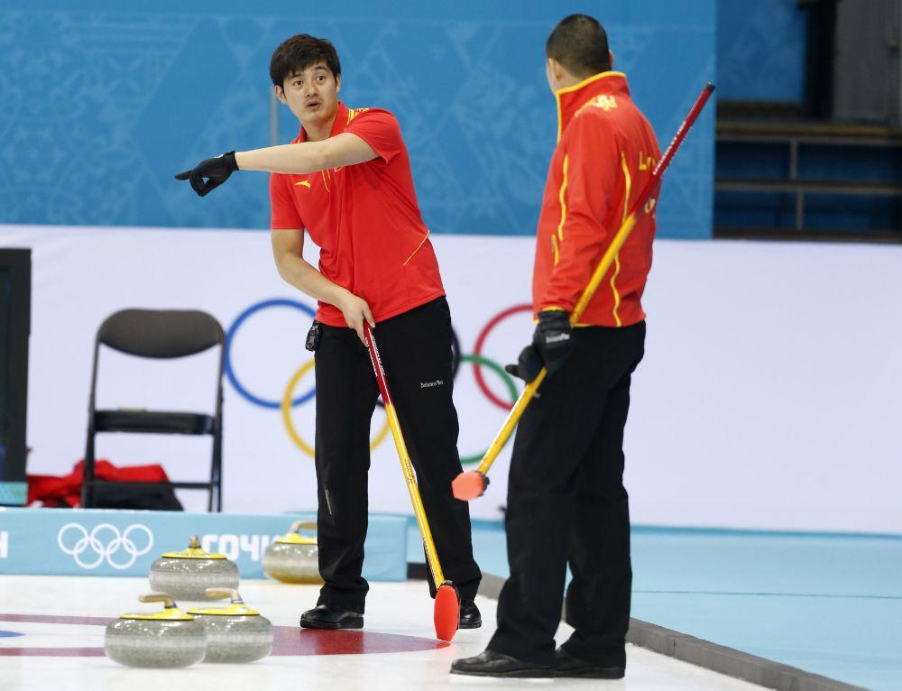 China's Xu Xiaoming, left, gives instructions to skip Liu Rui the 2014 Winter Olympics, Saturday, Feb. 8, 2014, in Sochi, Russia