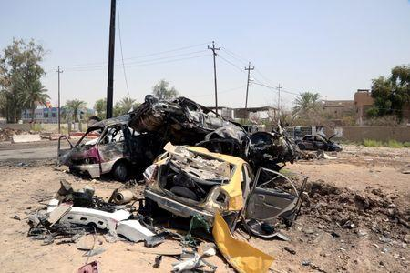 Destroyed vehicles are seen at the site of a suicide car bomber in Khalis, north of Baghdad, Iraq, July 25, 2016. REUTERS/Stringer