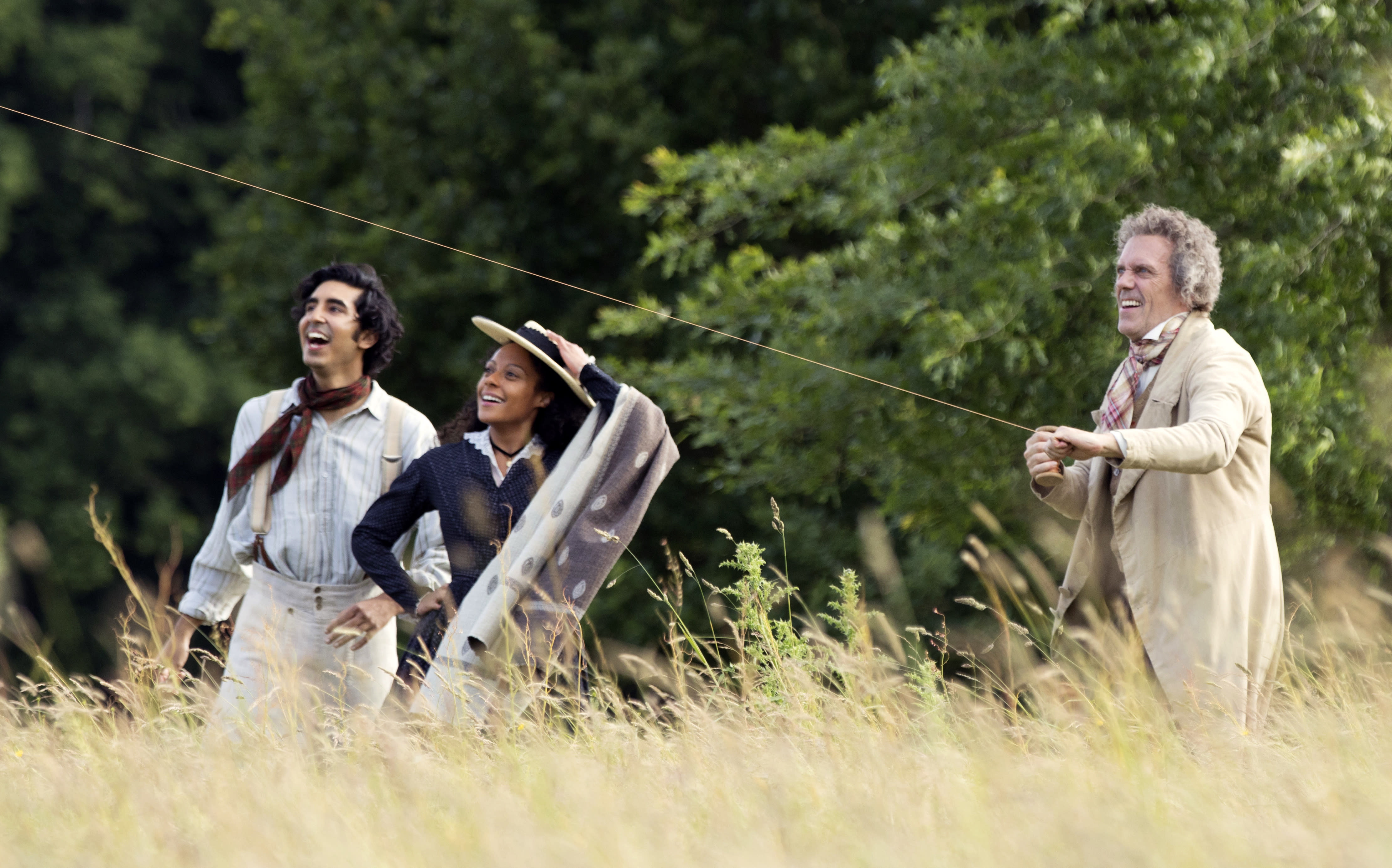 """This image released by Fox Searchlight Pictures shows Dev Patel, from left, Rosalind Eleazar and Hugh Laurie in a scene from the film """"The Personal History of David Copperfield."""" (Dean Rogers/Fox Searchlight Pictures via AP)"""