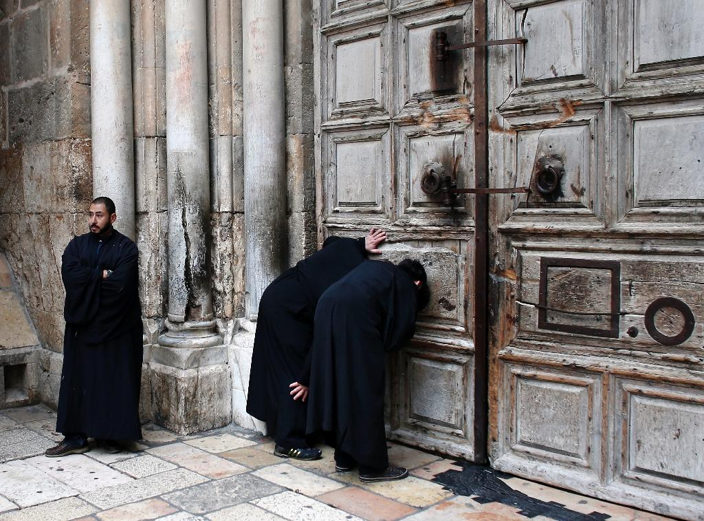 Christian Orthodox priests look through a hole in the main door of the Church of the Holy Sepulchre, before the Holy fire ceremony around Jesus' tomb, in Jerusalem's Old City during the Orthodox Easter ceremony of the 'Holy Fire' on April 11, 2015
