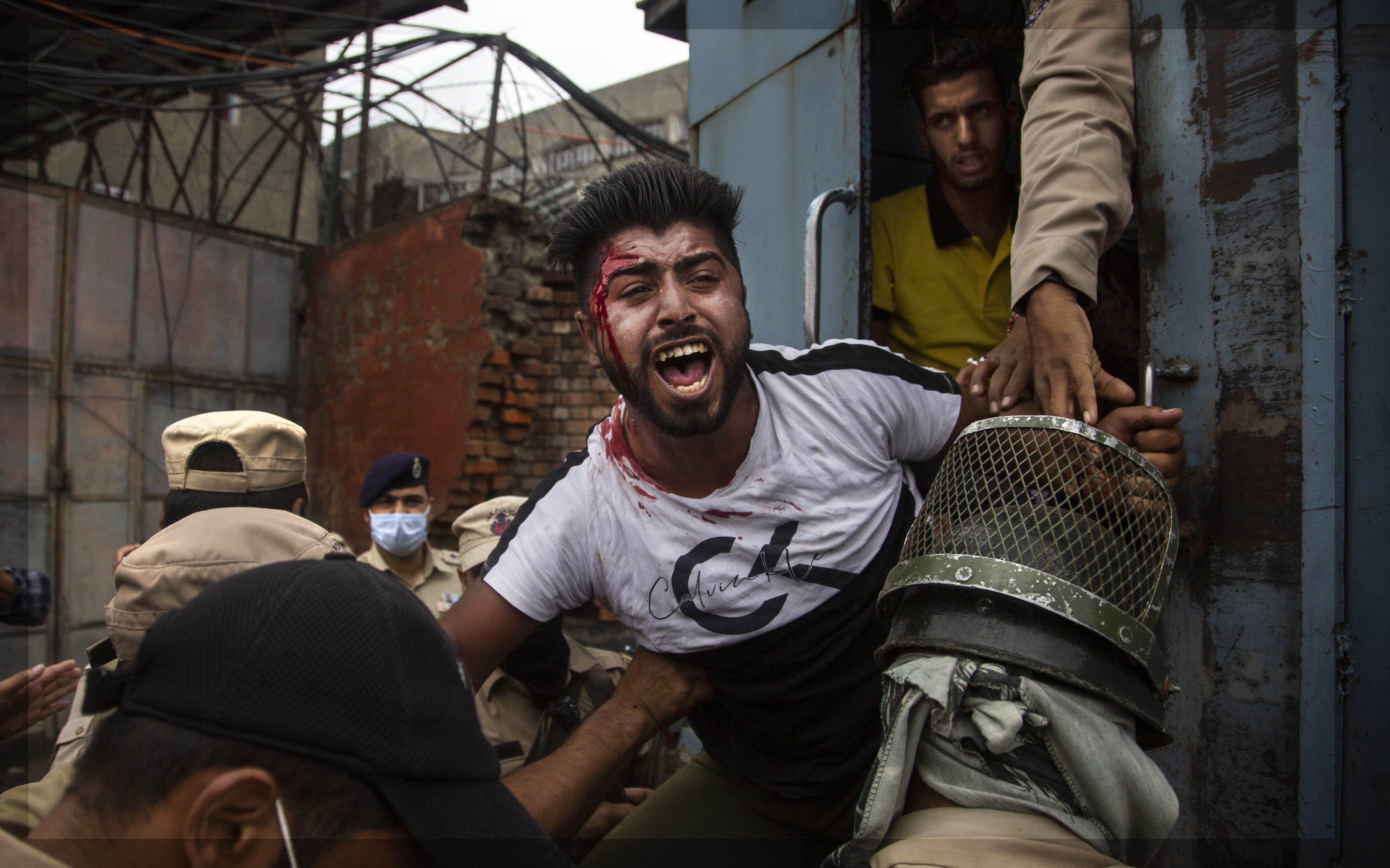 Indian policemen detain a Kashmiri Shiite Muslim as he attempt with others to take out a religious procession in Srinagar, Indian controlled Kashmir, Friday, Aug. 28, 2020. Police and paramilitary soldiers on Friday detain dozens of Muslims participating in religious processions in the Indian portion of Kashmir. Authorities had imposed restrictions in parts of Srinagar, the region's main city, to prevent gatherings marking Muharram from developing into anti-India protests. (AP Photo/Mukhtar Khan)