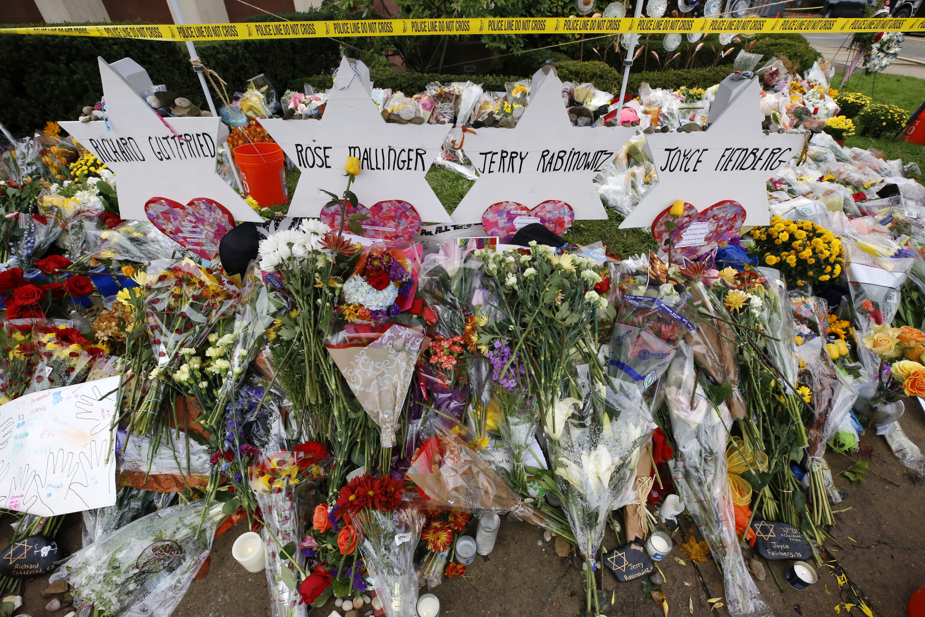 Flowers are pile around Stars of David Thursday, Nov. 1, 2018, at a makeshift memorial outside the Tree of Life Synagogue to the 11 people killed Oct 27, 2018 while worshipping in the Squirrel Hill neighborhood of Pittsburgh. (AP Photo/Gene J. Puskar)