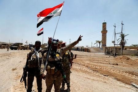 Iraqi security forces gesture in the town of Garma, Iraq, May 26, 2016.REUTERS/Thaier Al-Sudani