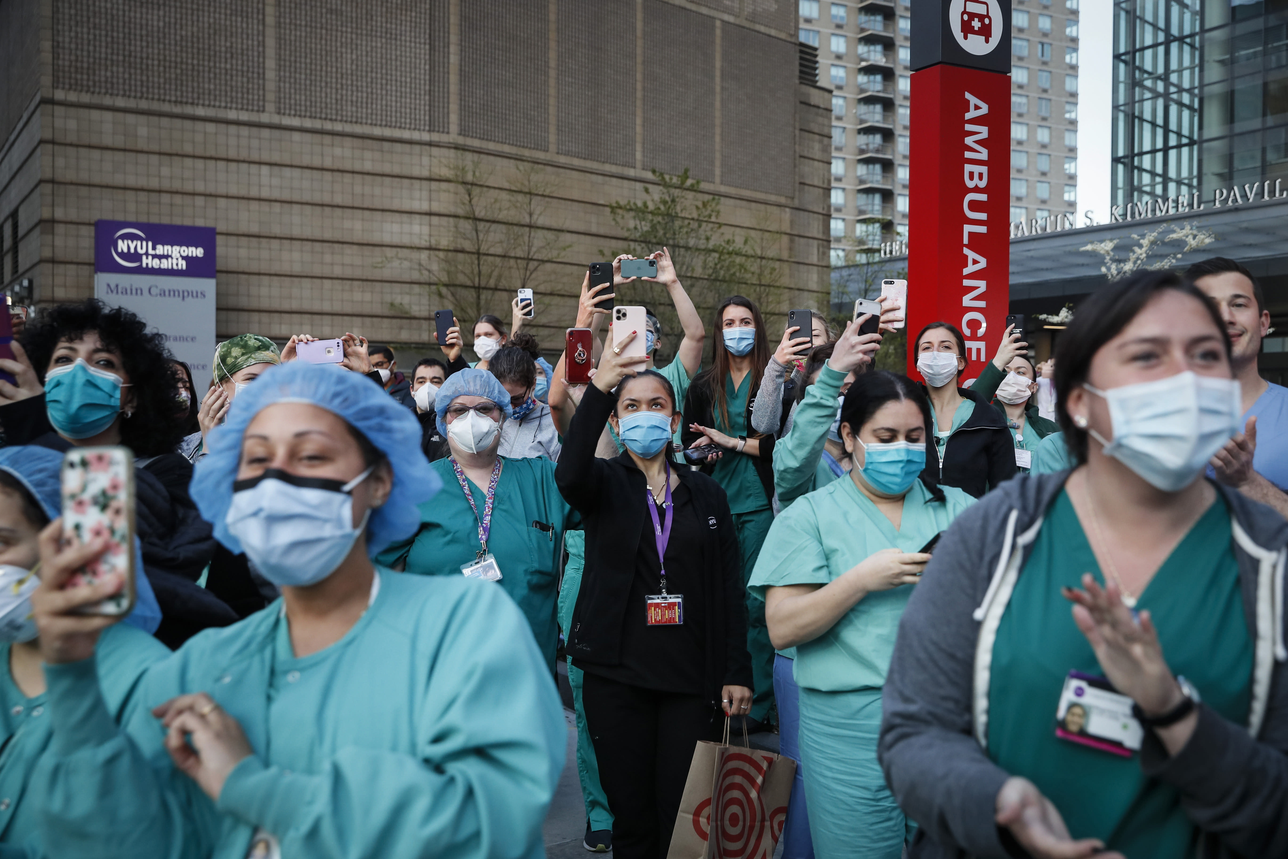 FILE - In this April 28, 2020, file photo Medical personnel attend a daily 7 p.m. applause in their honor, during the coronavirus pandemic outside NYU Langone Medical Center in the Manhattan borough of New York. Nurses on the front lines of New York's COVID-19 pandemic are calling for the state to enact minimum staffing standards ahead of another wave of infections. (AP Photo/John Minchillo, File)
