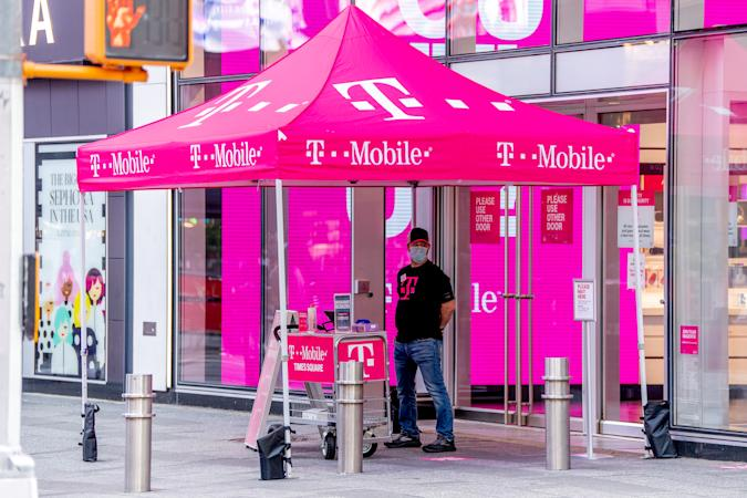 NEW YORK, NEW YORK - AUGUST 18: A clerk at the T-Mobile store in Times Square provides curb side service during the fourth phase of the coronavirus reopening on August 18, 2020 in New York, New York. The fourth phase allows outdoor arts and entertainment, sporting events without fans and media production. (Photo by Roy Rochlin/Getty Images)