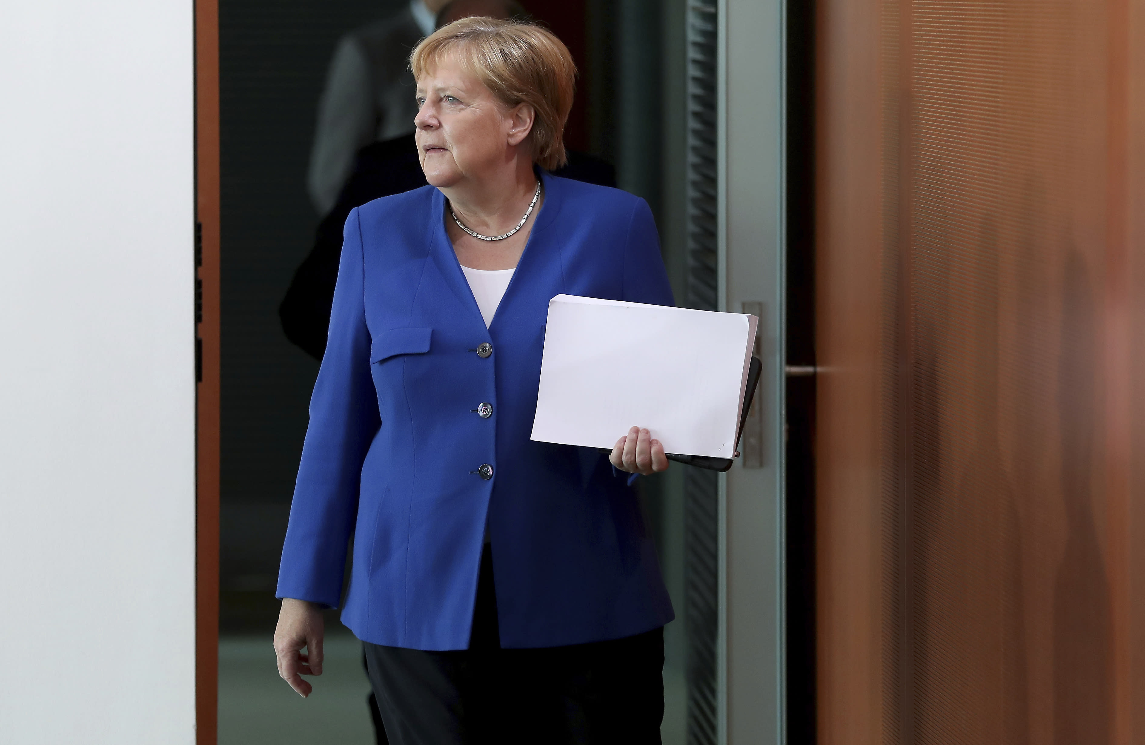 German Chancellor Angela Merkel arrives for the weekly cabinet meeting at the Chancellery in Berlin, Germany, Wednesday, Aug. 21, 2019. The German government sold 30-year bonds at a negative interest rate Wednesday Aug. 21, 2019, in a sign of the clouds over markets and future growth as well as increased expectations that more central bank stimulus is likely on the way.(AP Photo/Michael Sohn)