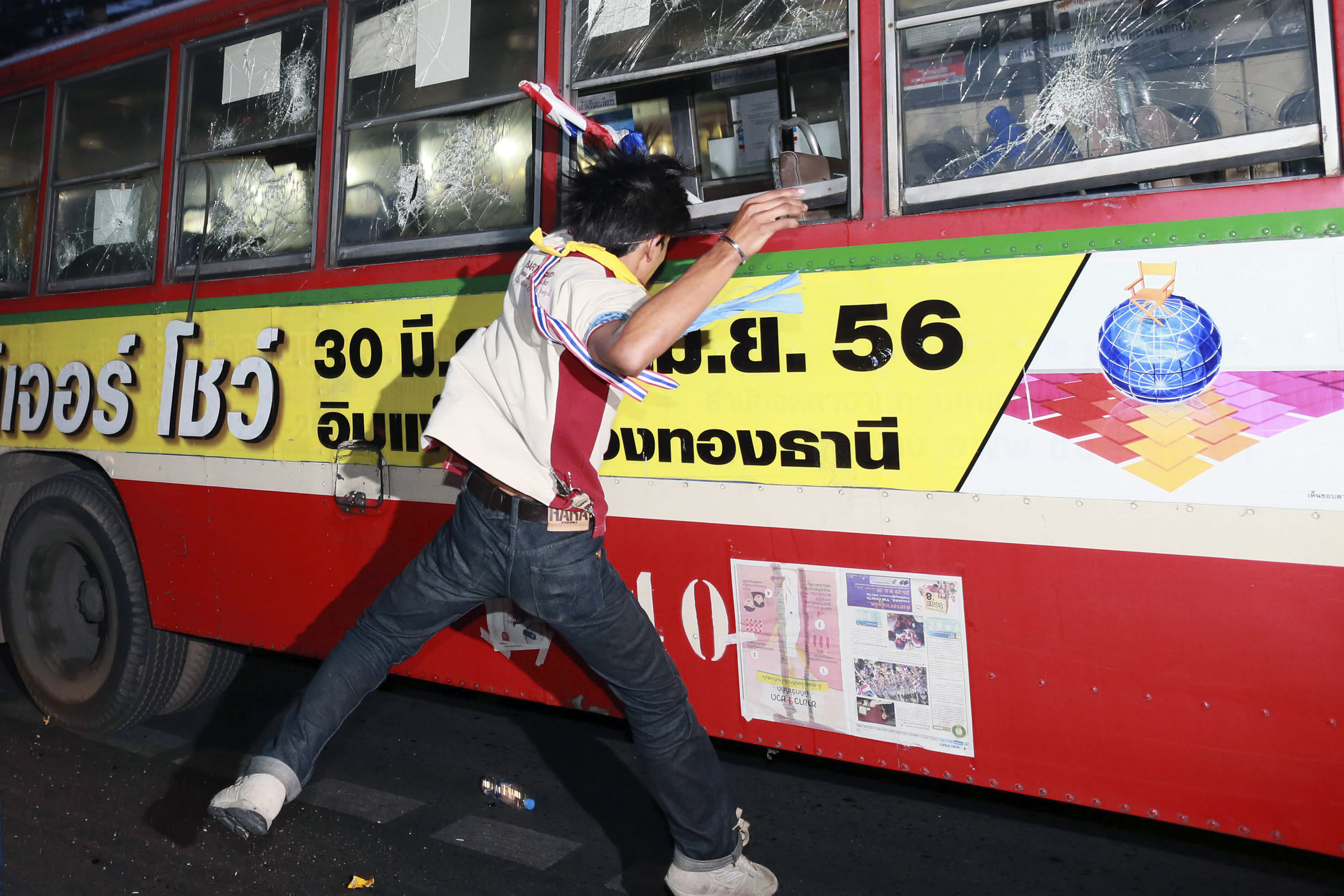 An anti-government protester attacks people they suspected of supporting the current Thai government on the bus in Bangkok,Thailand Saturday, Nov. 30, 2013. A mob of anti-government protesters smashed the windows of a moving Bangkok bus Saturday in the first eruption of violence after a week of tense street protests.(AP Photo/Wason Wanichakorn)