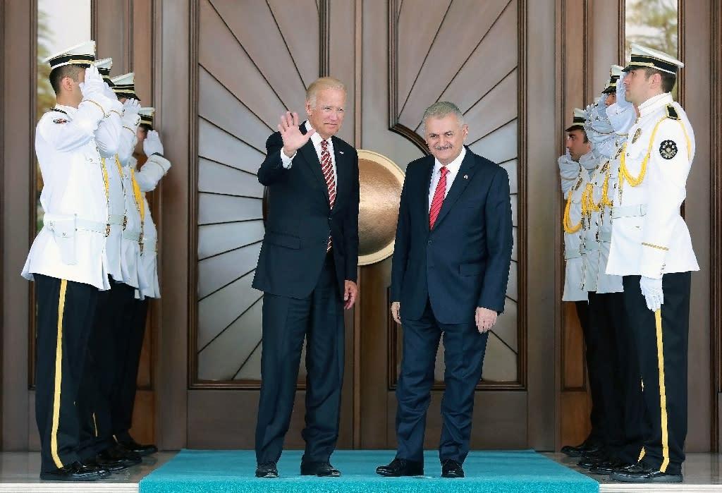 US Vice President Joe Biden waves next to Turkish Prime Minister Binali Yildirim (R) before their meeting at Cankaya Palace in Ankara, on August 24, 2016 (AFP Photo/Adem Altan)
