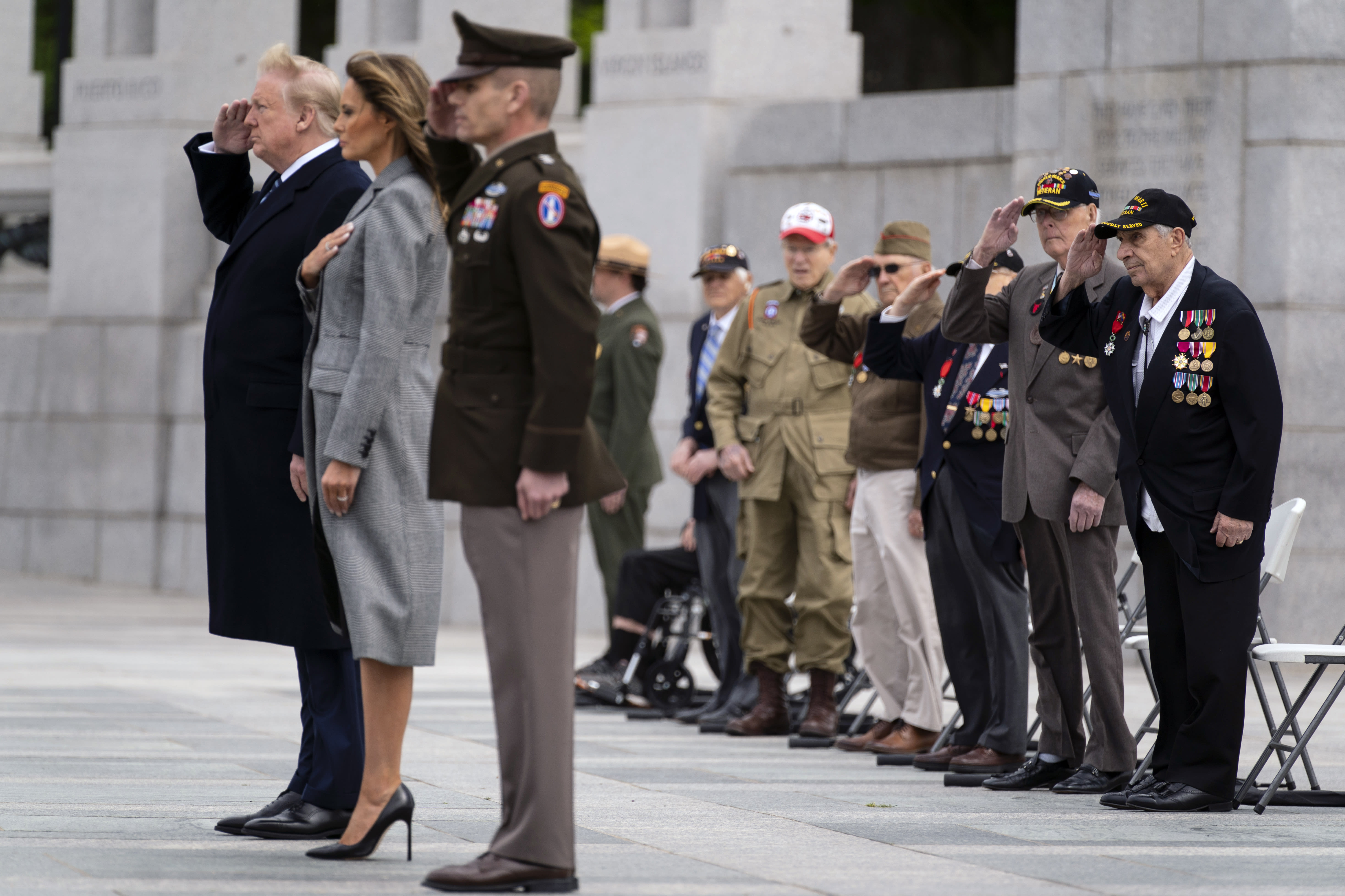 World War II veterans salute as Taps is played during a ceremony at the World War II Memorial to commemorate the 75th anniversary of Victory in Europe Day with President Donald Trump and first lady Melania Trump, Friday, May 8, 2020, in Washington. (AP Photo/Evan Vucci)