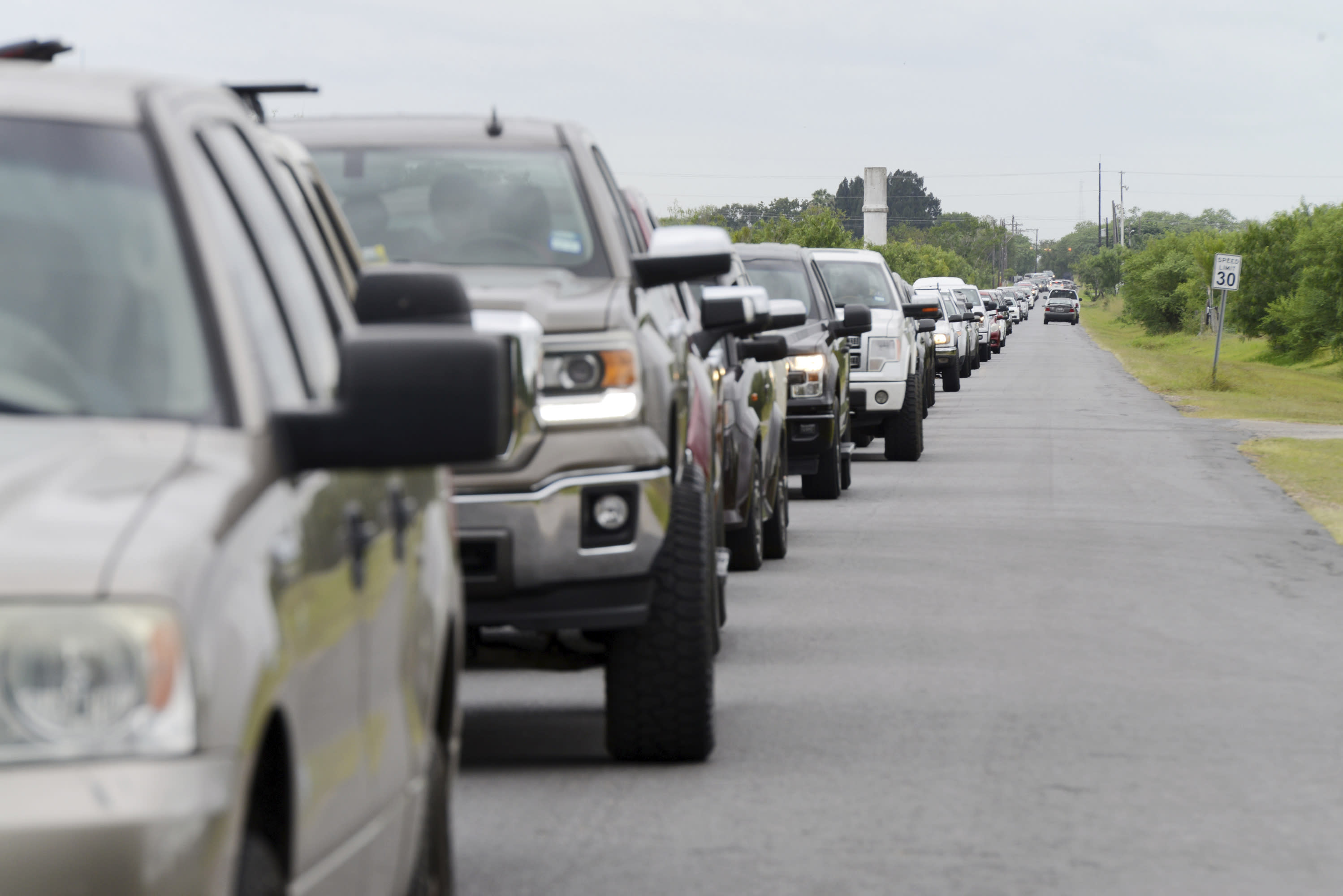 Hundreds of vehicles form a line as Brownsville, Texas residents wait for sandbags Saturday, July 25, 2020, at Anastacio Guillen Precinct 1 Cameron County Public Works Building along Browne Avenue as South Texas prepare for torrential rainfall due to Hurricane Hanna. (Miguel Roberts/The Brownsville Herald via AP)