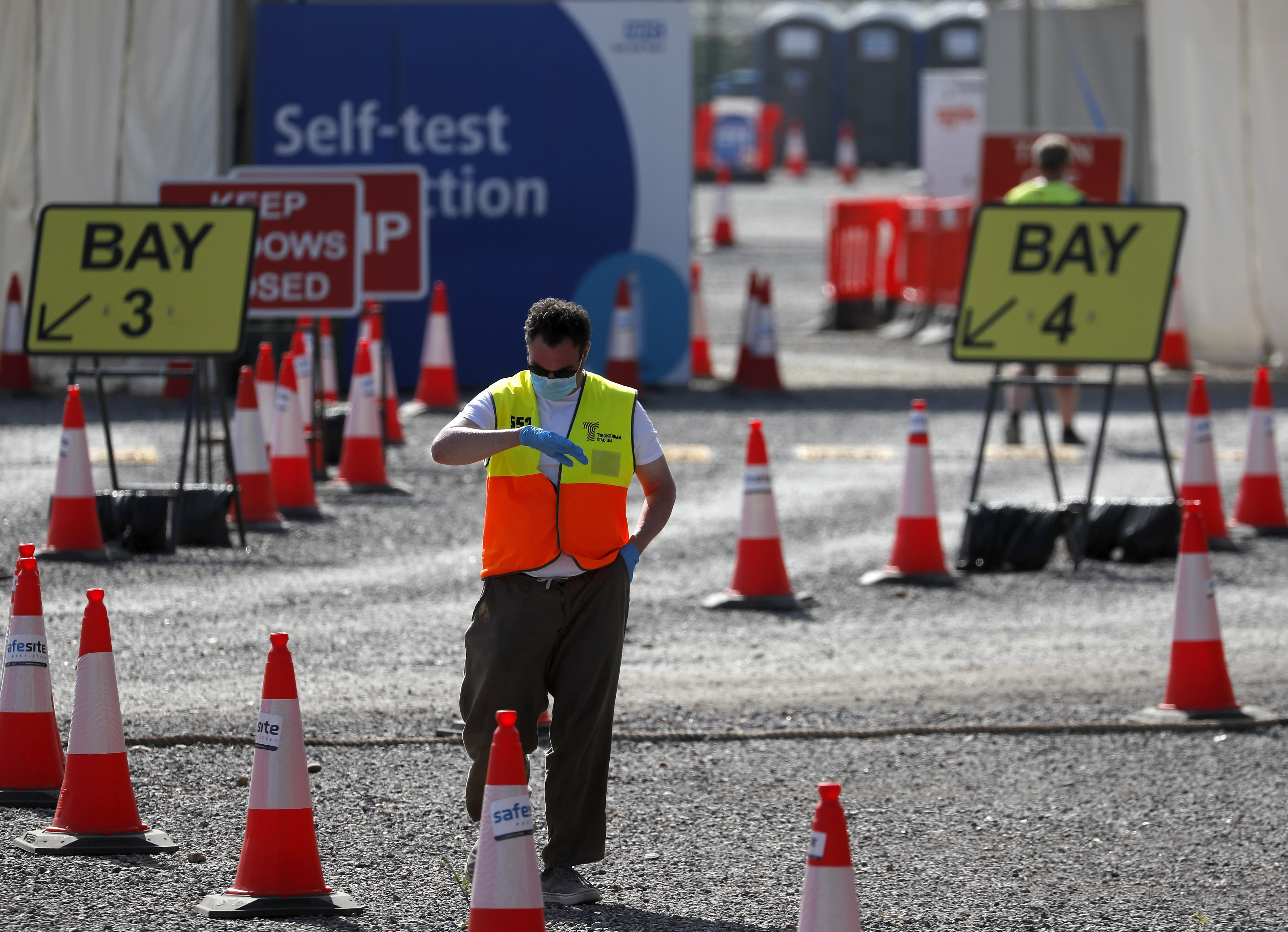 A staff member waits at empty lanes of a Covid-19 drive thru testing facility at Twickenham stadium in London, Thursday, Sept. 17, 2020. Britain has imposed tougher restrictions on people and businesses in parts of northeastern England on Thursday as the nation attempts to stem the spread of COVID-19, although some testing facilities remain under-utilised. (AP Photo/Frank Augstein)