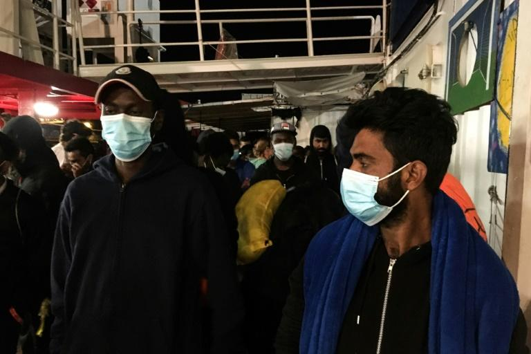 Police escorted the migrants a short distance to another ship, where they will be quarantined to prevent the possible spread of coronavirus (AFP Photo/Shahzad ABDUL)