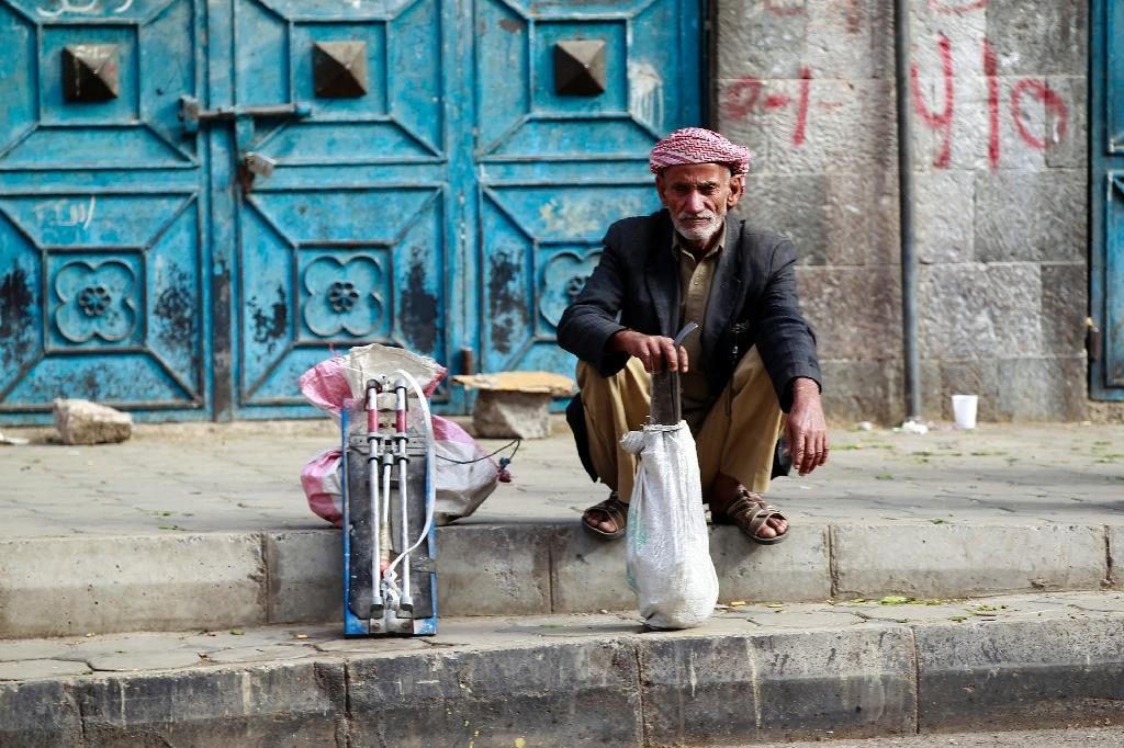 An unemployed Yemeni manual laborer waits for work offers on a sidewalk in Sanaa (AFP Photo/Mohammed Huwais)